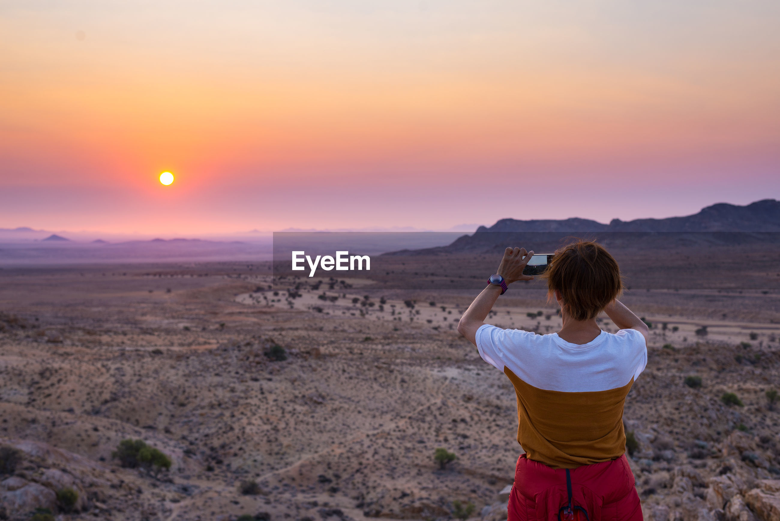 Rear view of woman photographing sunset