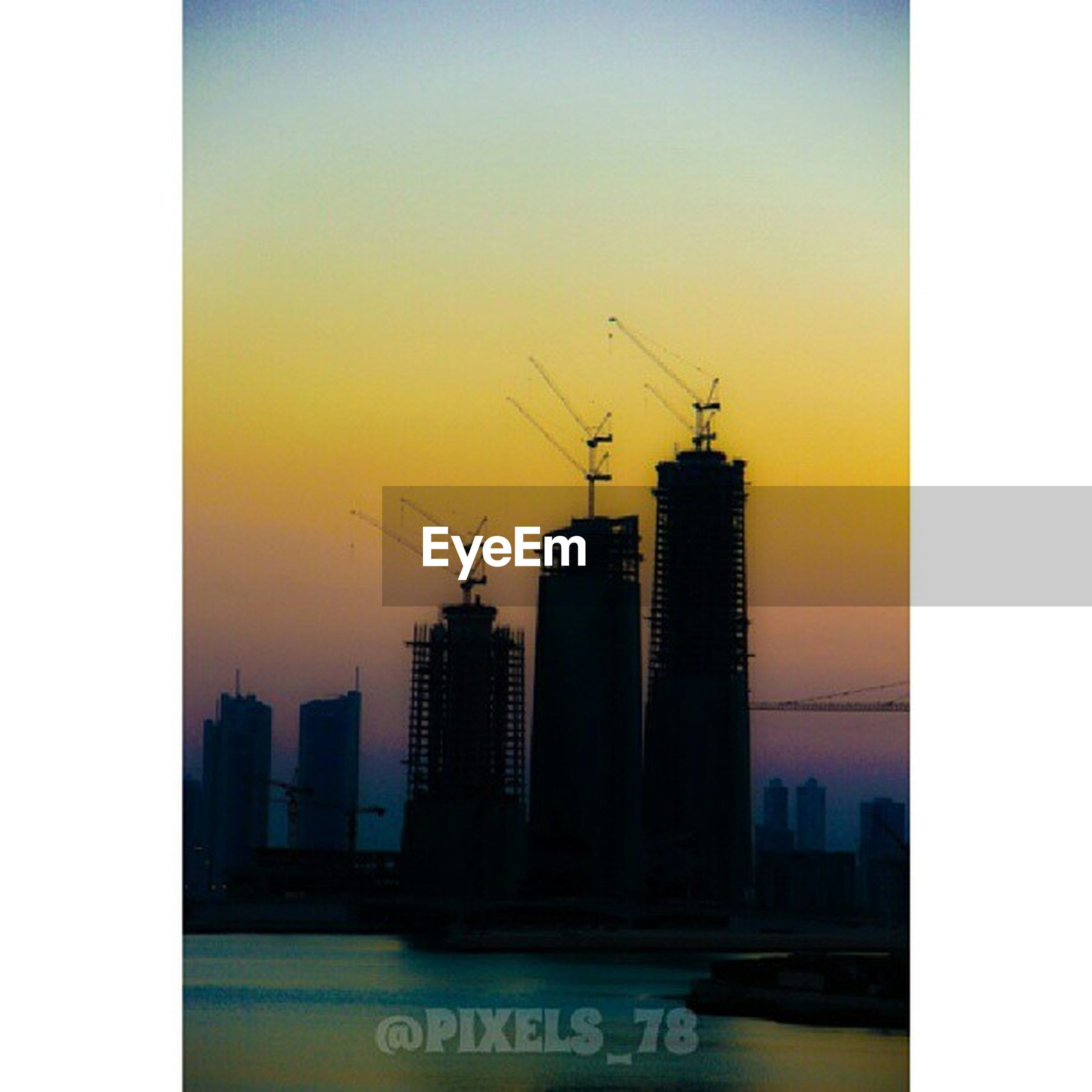 building exterior, architecture, built structure, sunset, city, skyscraper, transfer print, silhouette, development, auto post production filter, clear sky, tower, crane - construction machinery, sky, orange color, tall - high, cityscape, building, urban skyline, office building