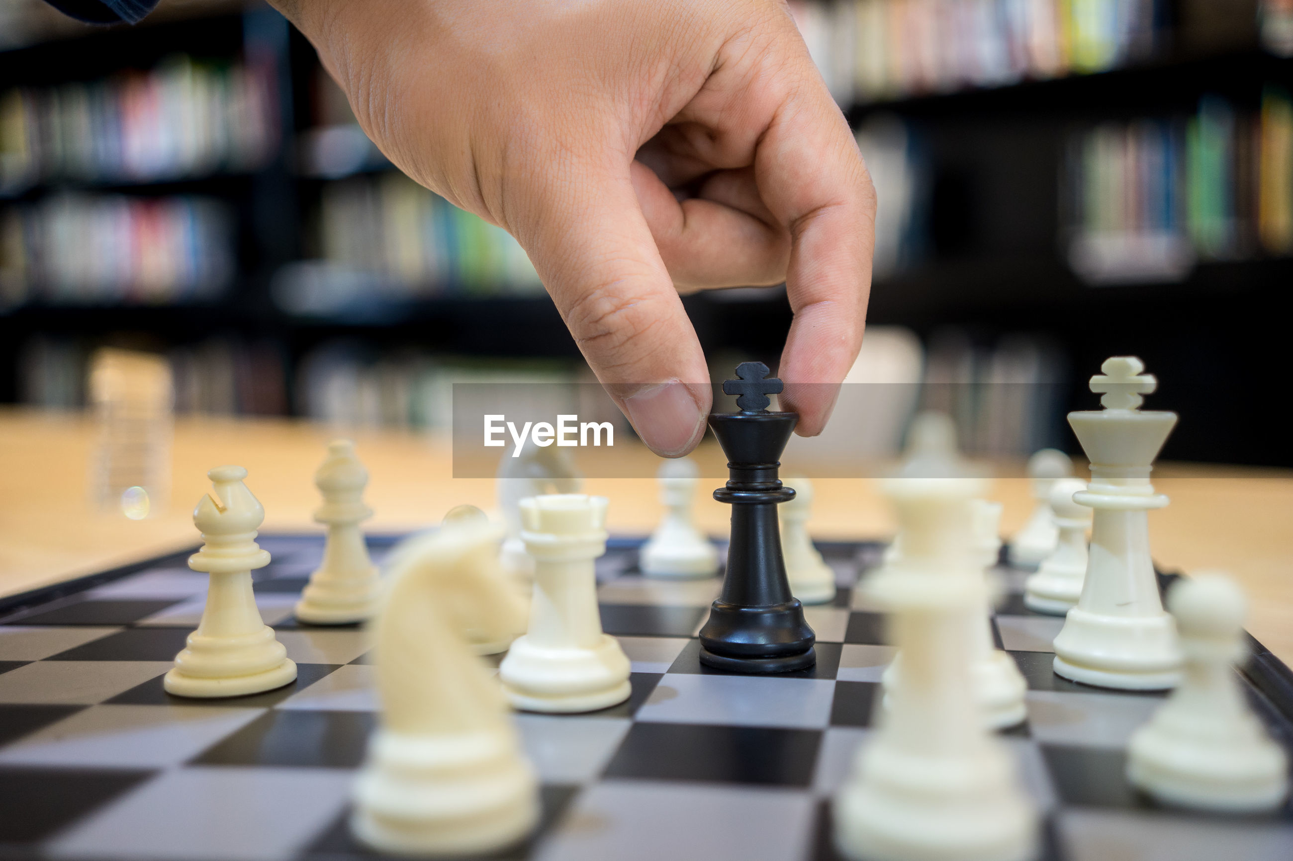 Cropped hand of man playing chess on table in library