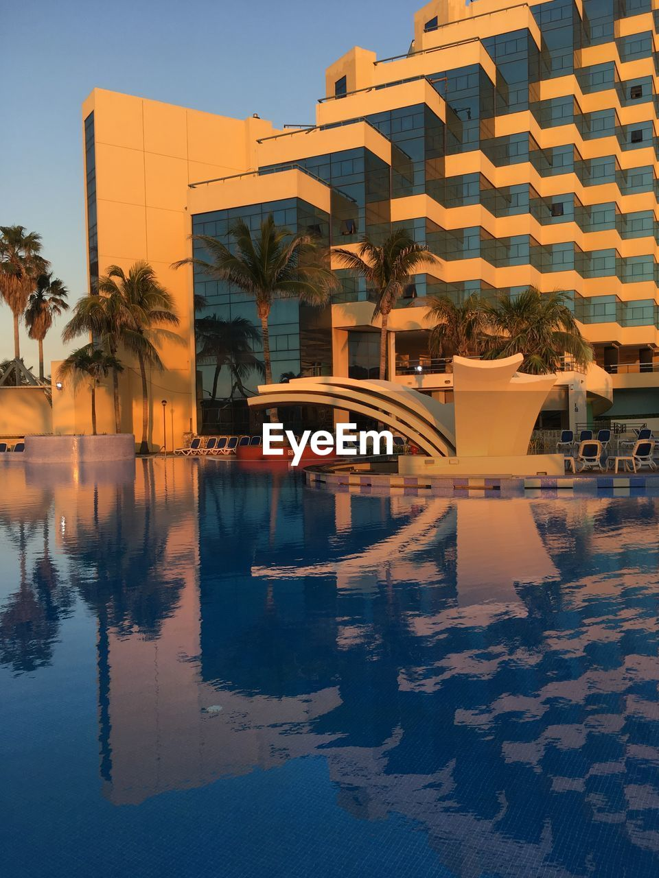 architecture, reflection, building exterior, built structure, water, modern, sunset, outdoors, city, swimming pool, no people, sky, day
