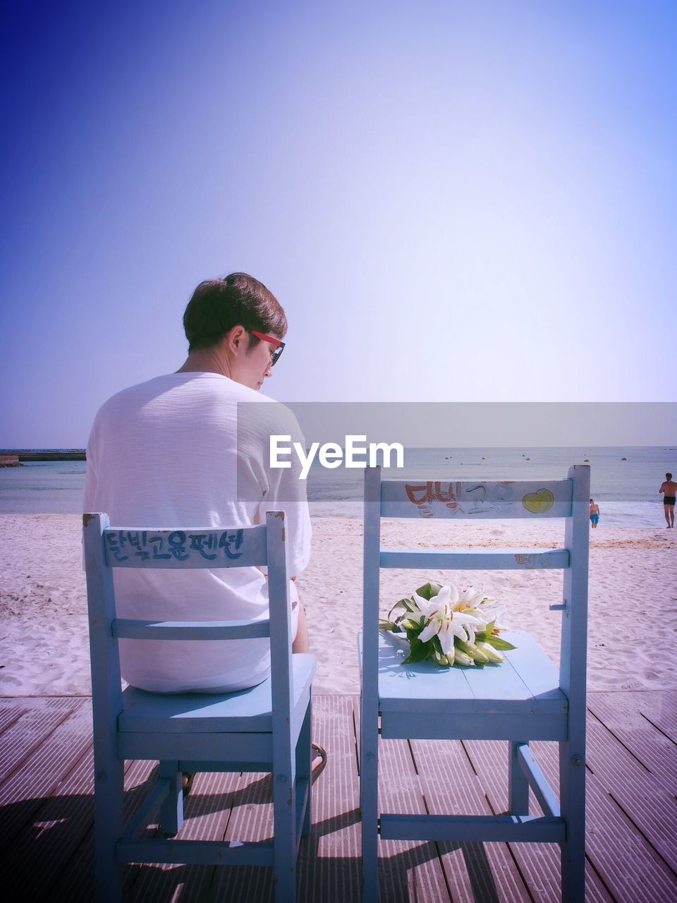 Rear view of man looking at lily flowers on wooden chair at beach against clear sky
