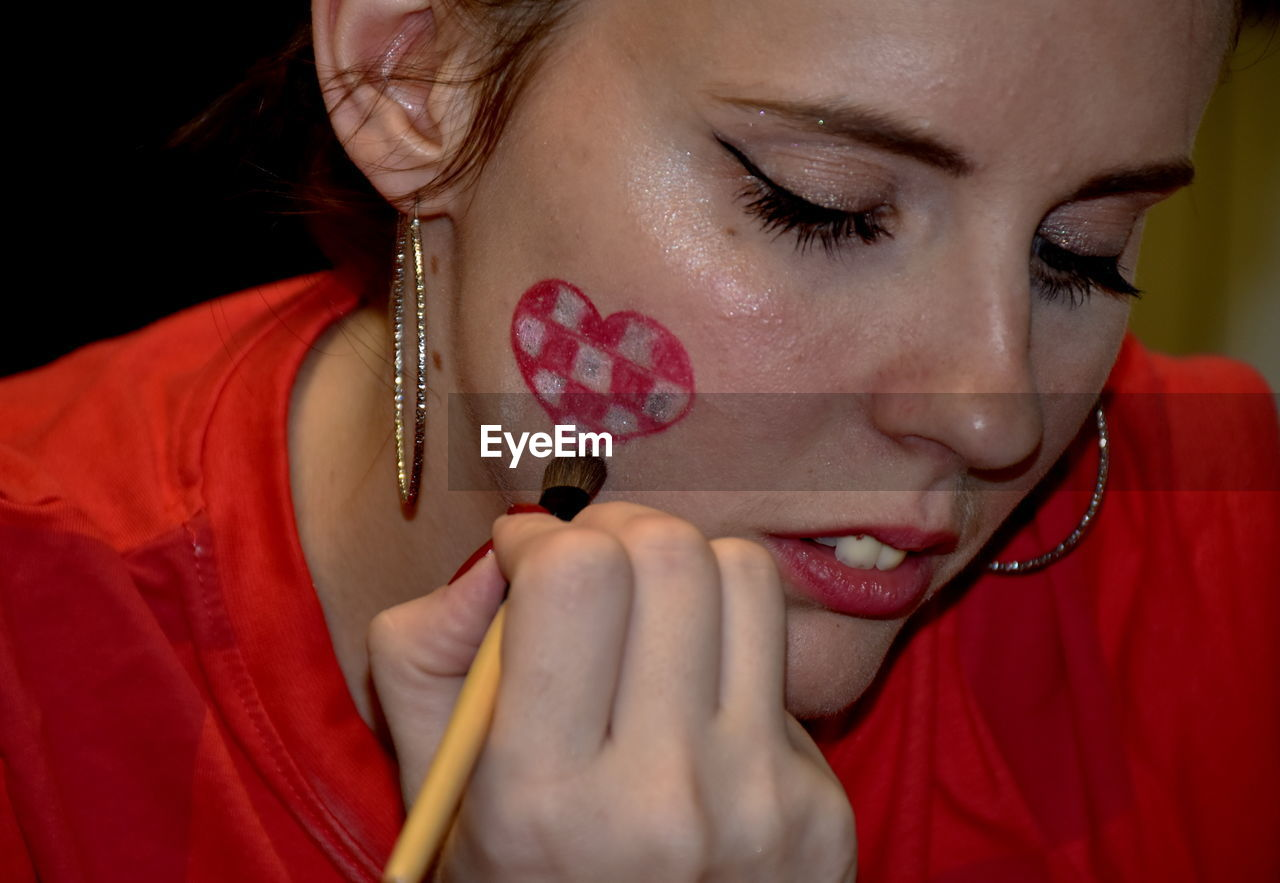 Close-up of woman making heart shape on cheek
