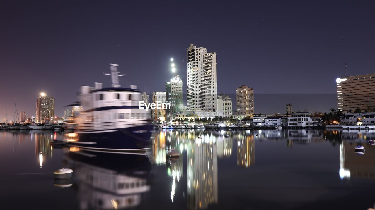illuminated, architecture, building exterior, night, built structure, reflection, skyscraper, water, city, waterfront, sky, tower, nautical vessel, modern, travel destinations, urban skyline, no people, transportation, outdoors, moored, clear sky, cityscape, sea, nature