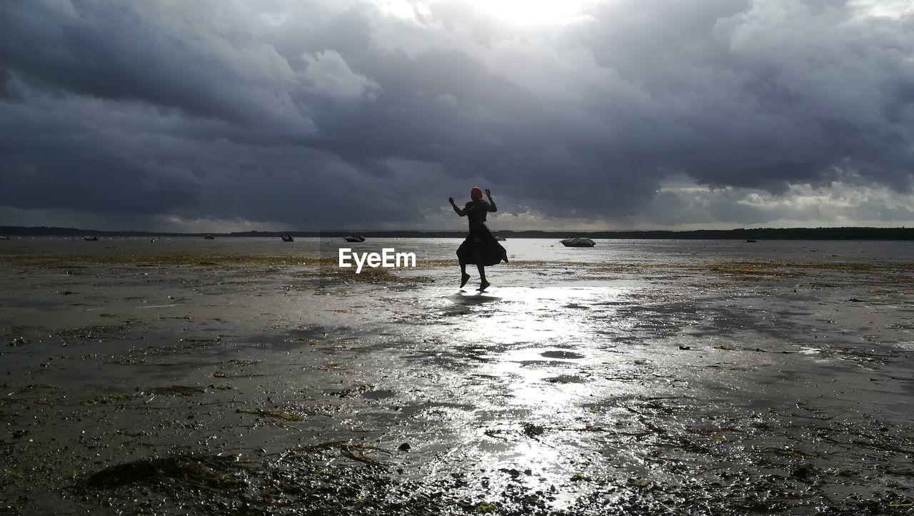 Woman dancing at beach against cloudy sky