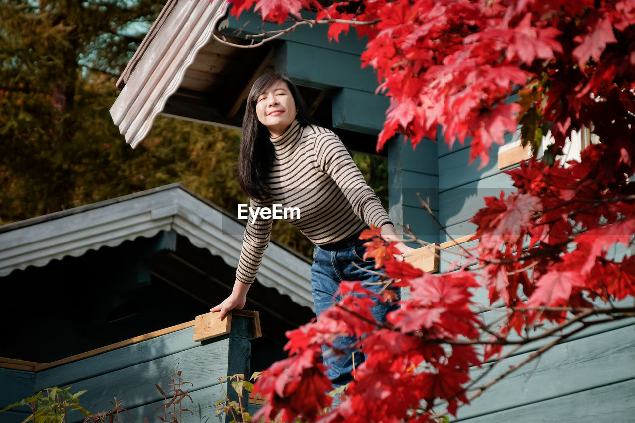 Low Angle View Of Woman Standing Against House