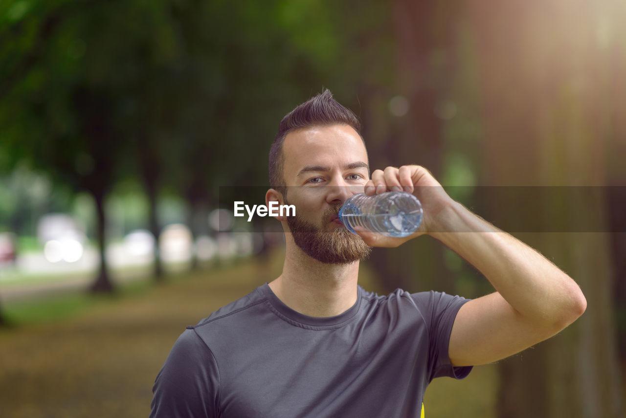 Portrait Of Handsome Athlete Drinking Water In Park