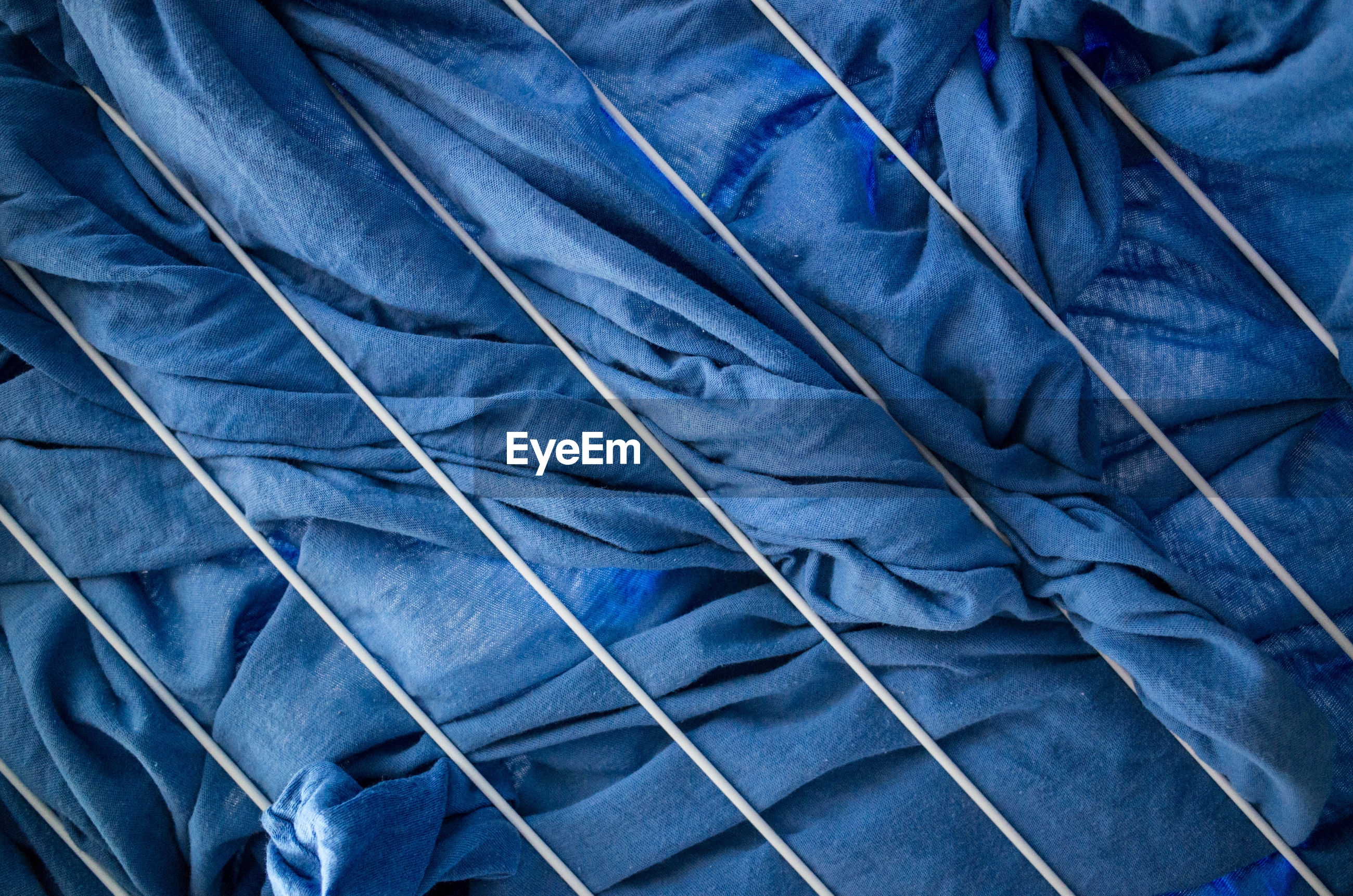 Low angle view of blue fabric on rope