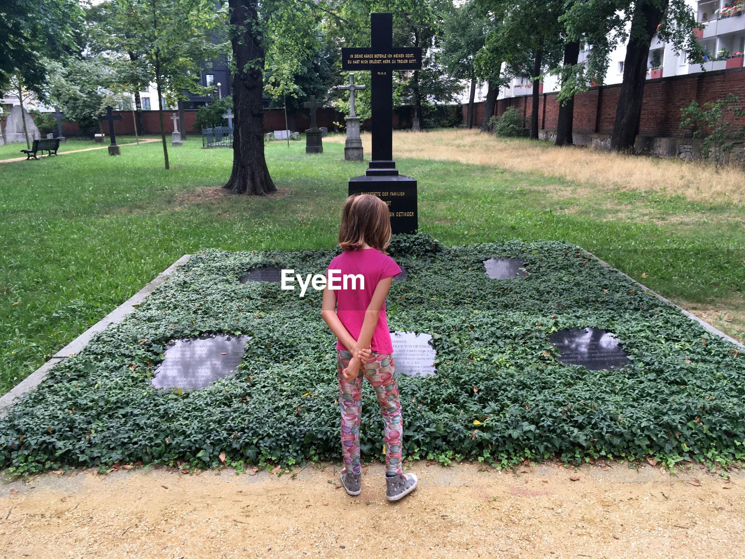 Full length rear view of girl standing in cemetery