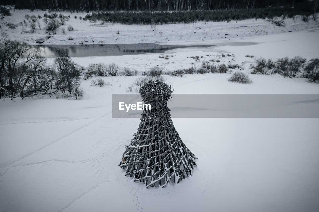 Snow covered land and trees on field