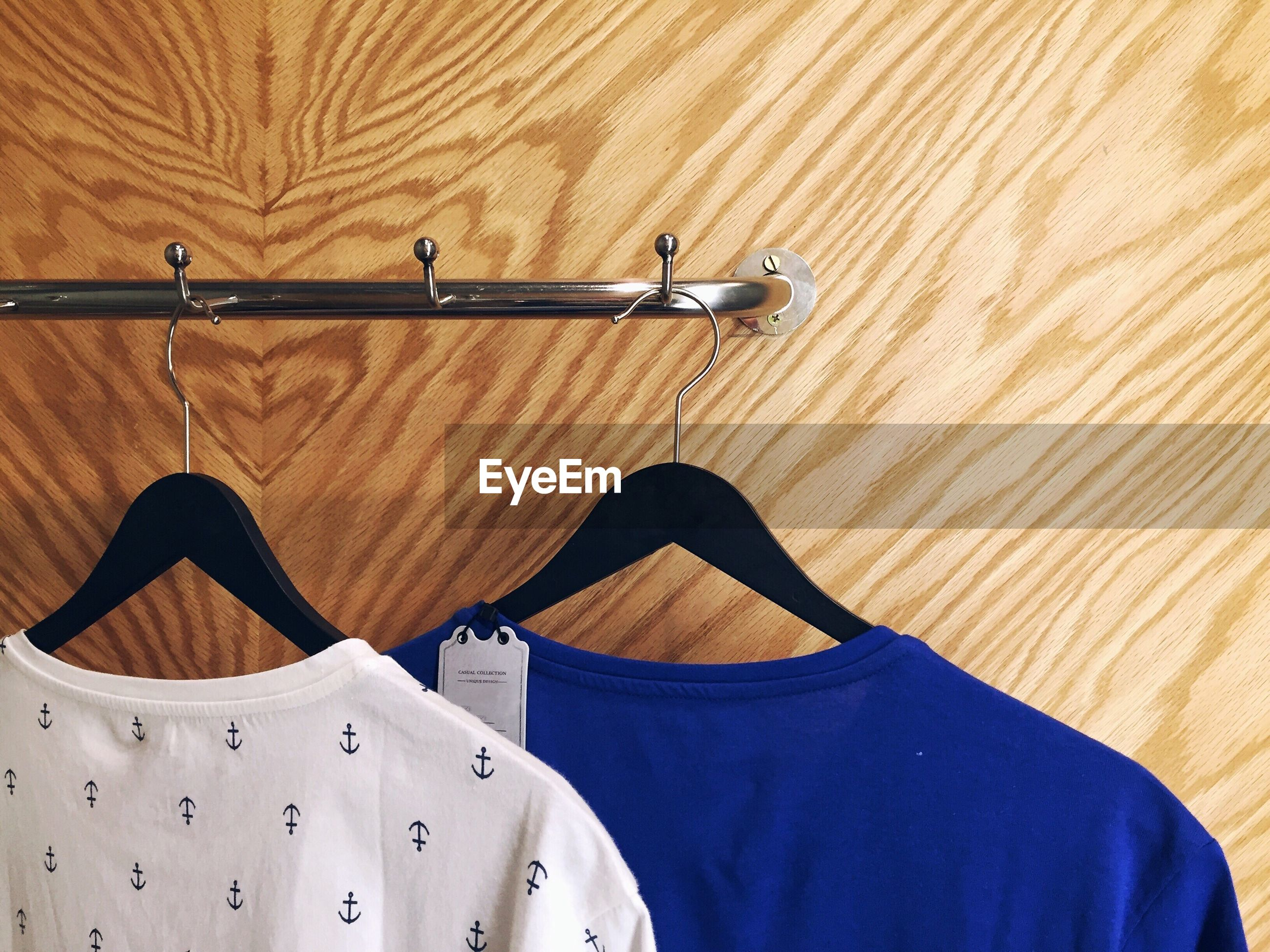 CLOSE-UP OF CLOTHES HANGING ON WOOD IN SHELF