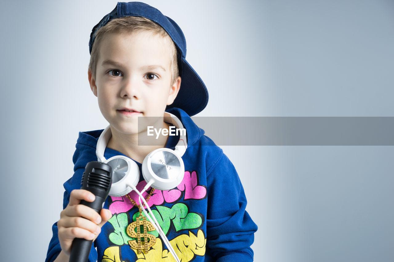Studio Shot Of Boy With Microphone And Headphones