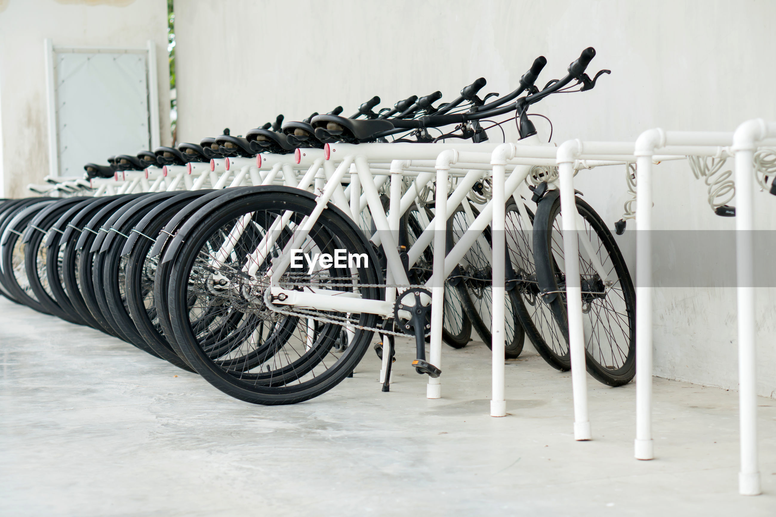 Bicycles parked on rack against white wall