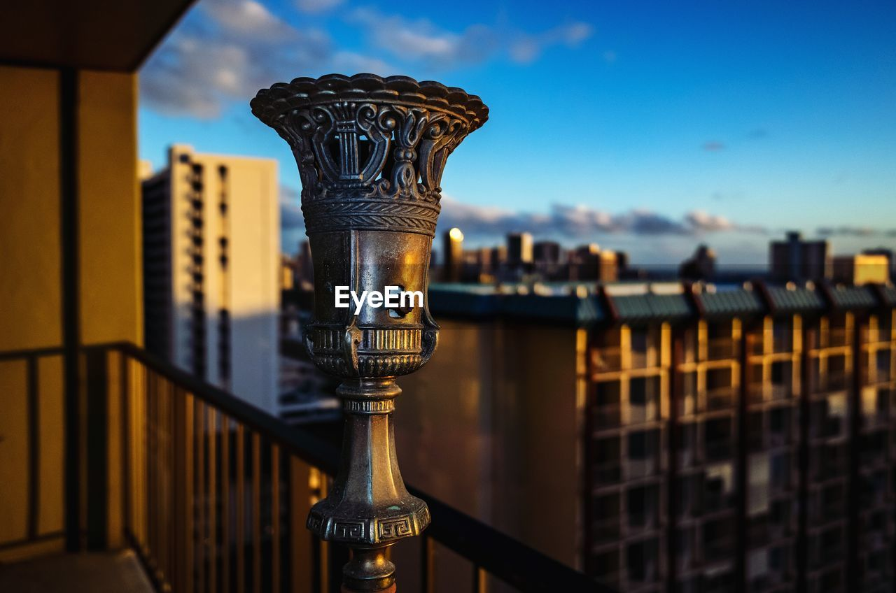 architecture, built structure, focus on foreground, building exterior, metal, sky, water, no people, binoculars, close-up, railing, nature, city, cityscape, building, coin operated, outdoors, day, coin-operated binoculars
