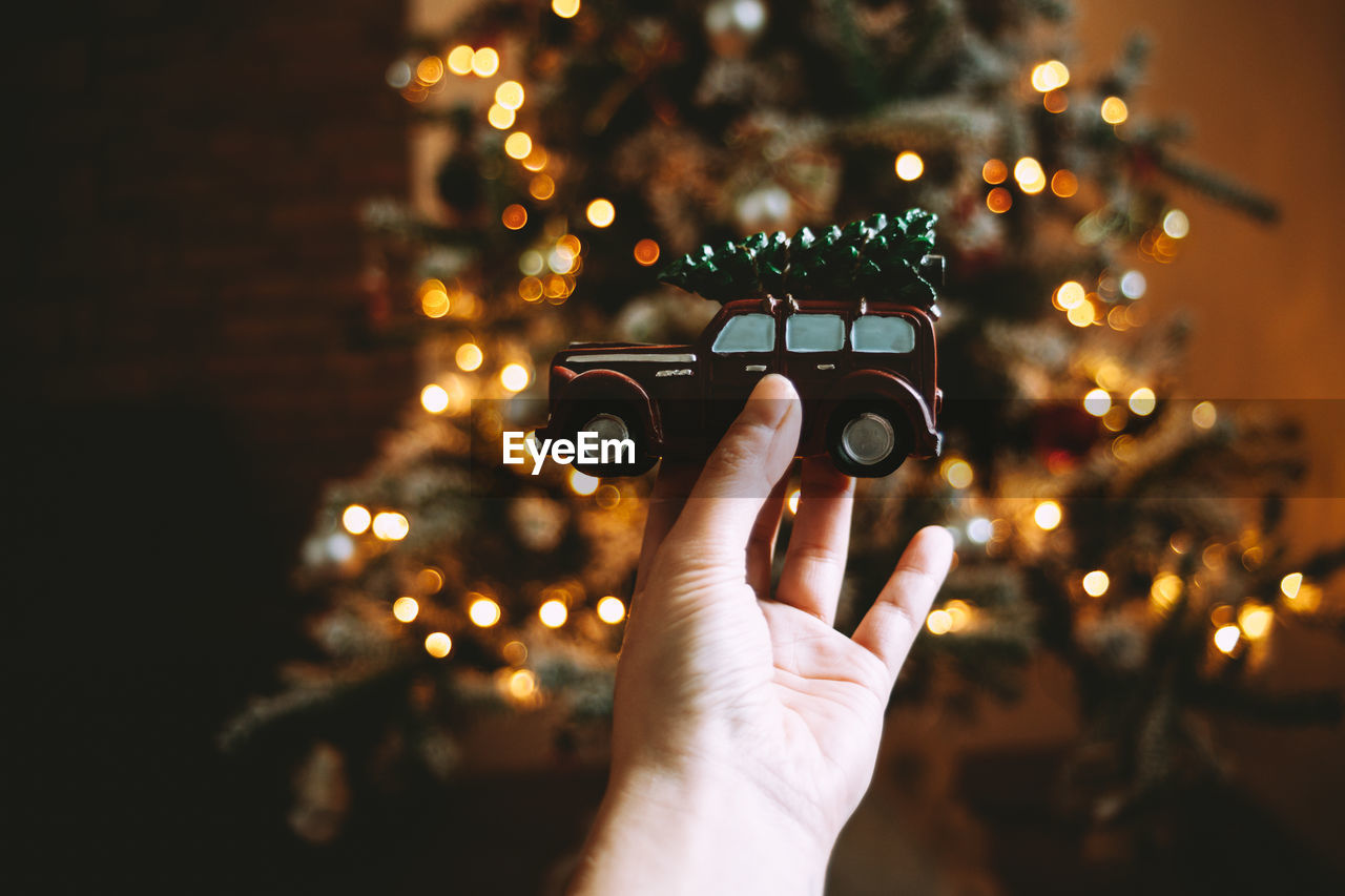 Cropped Hand Of Woman Holding Toy Car Against Illuminated Christmas Tree