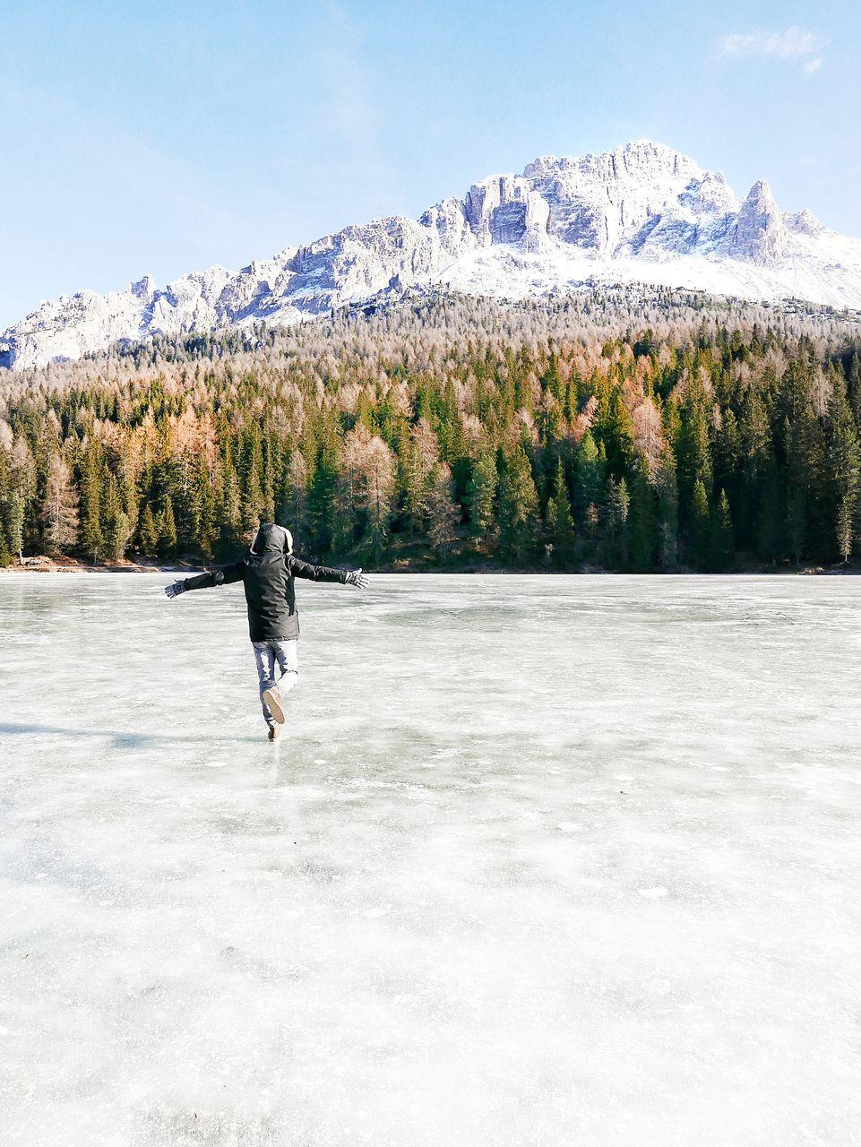 Full length of man running on frozen lake against forest