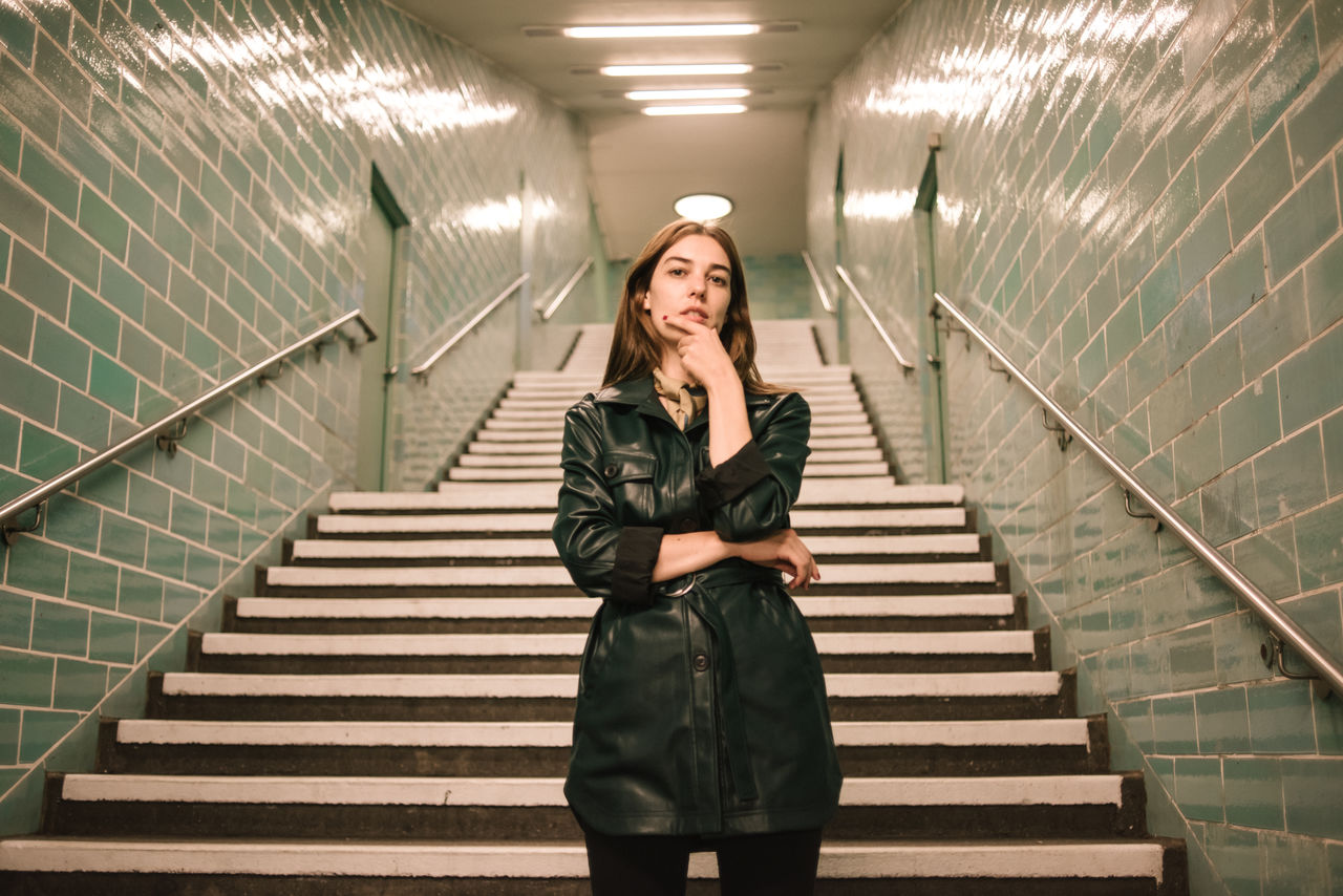 Portrait of young woman standing on steps at subway station