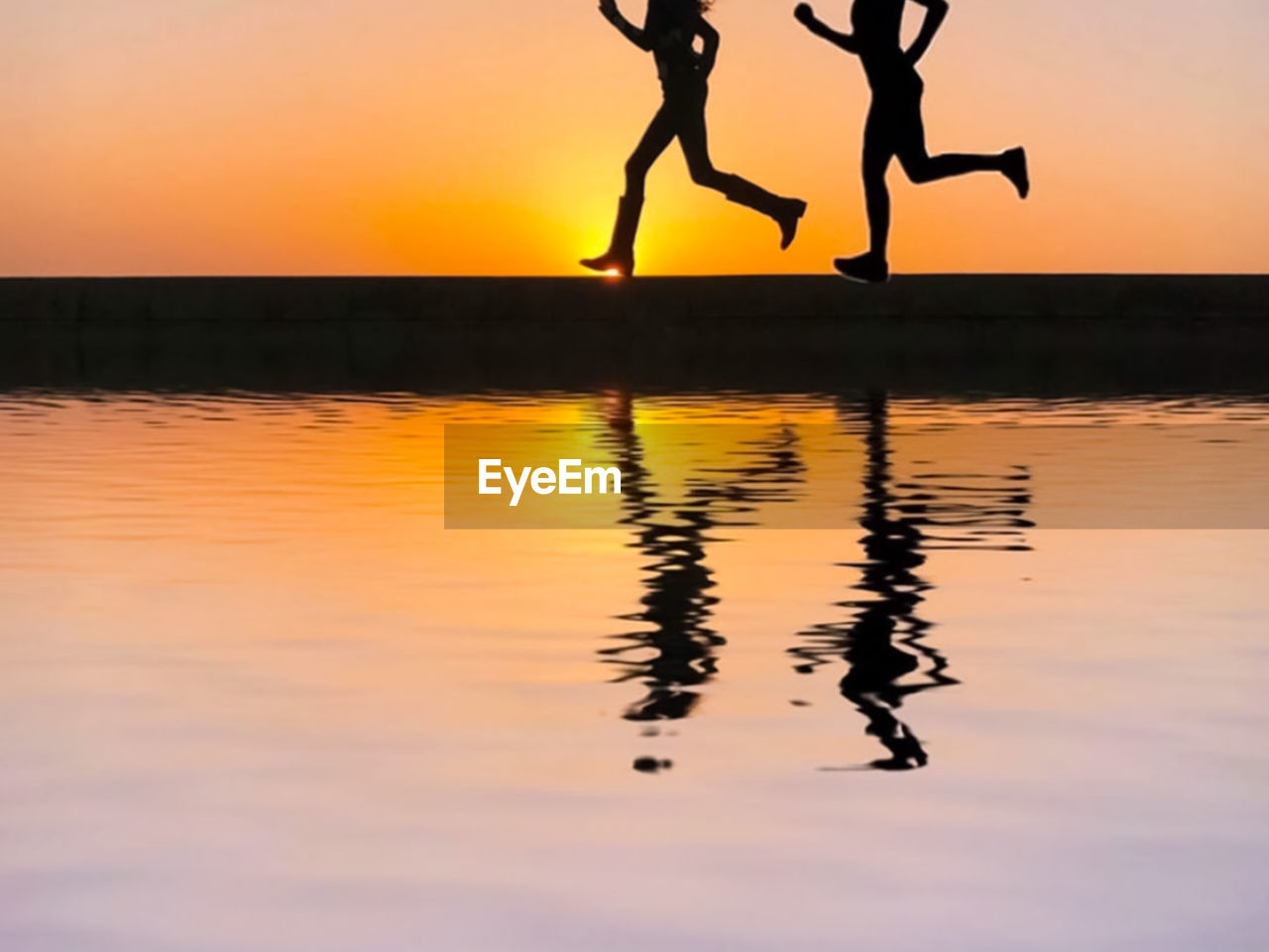 Low section of silhouette women running by lake against sky during sunset