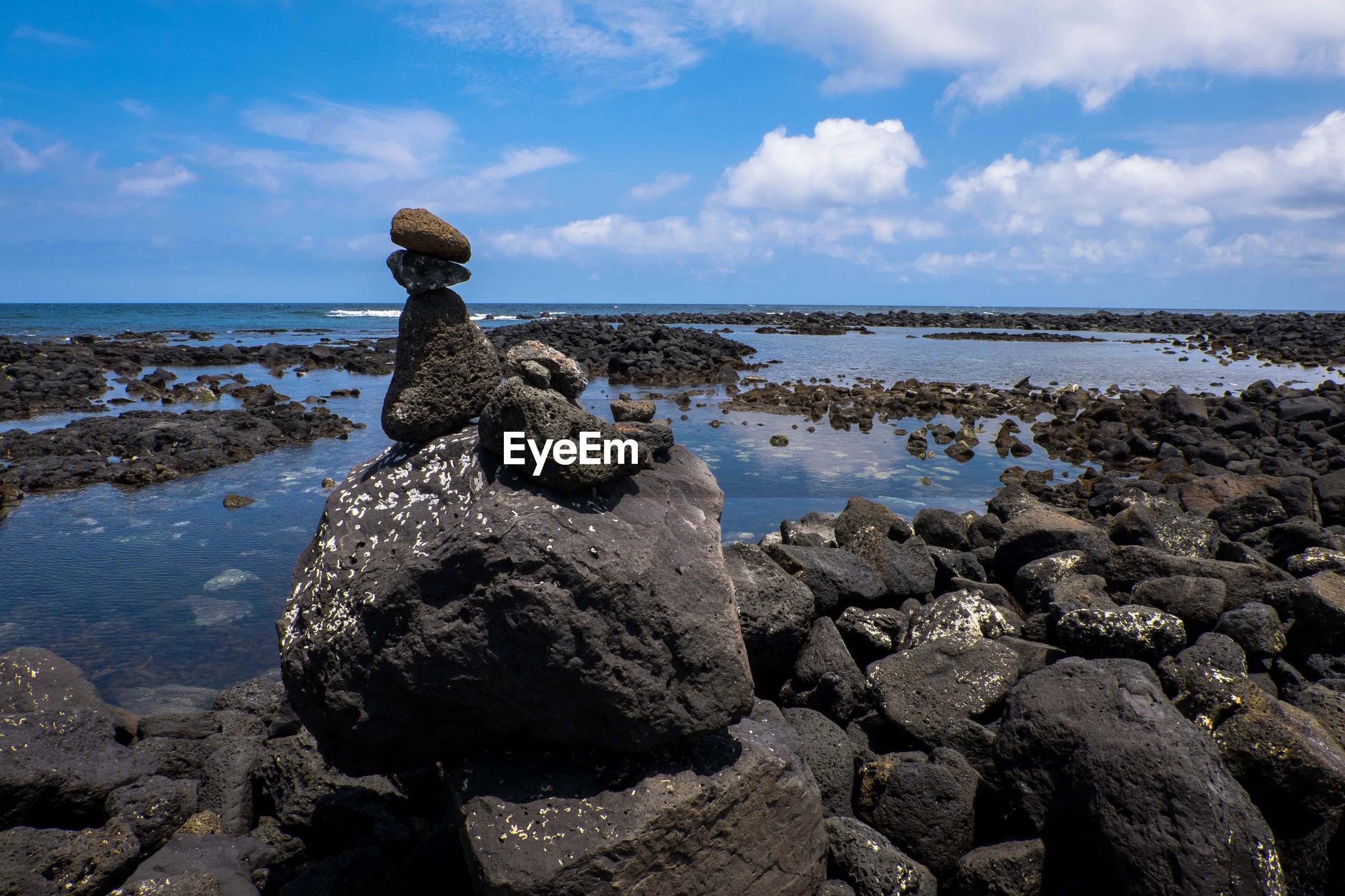 STONE ON BEACH AGAINST SKY