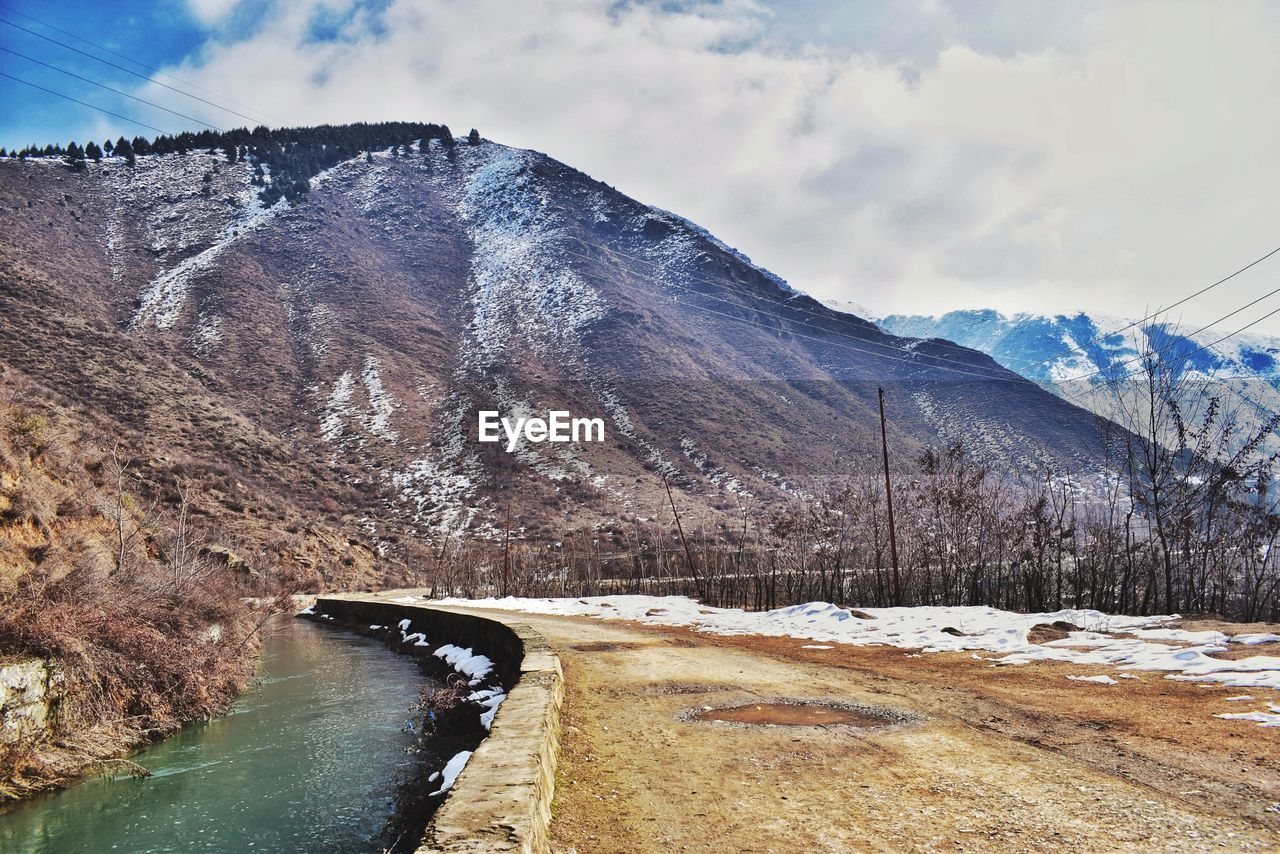 mountain, sky, scenics - nature, beauty in nature, water, nature, cold temperature, day, winter, mountain range, tranquil scene, snow, no people, cloud - sky, tranquility, environment, non-urban scene, transportation, outdoors, snowcapped mountain