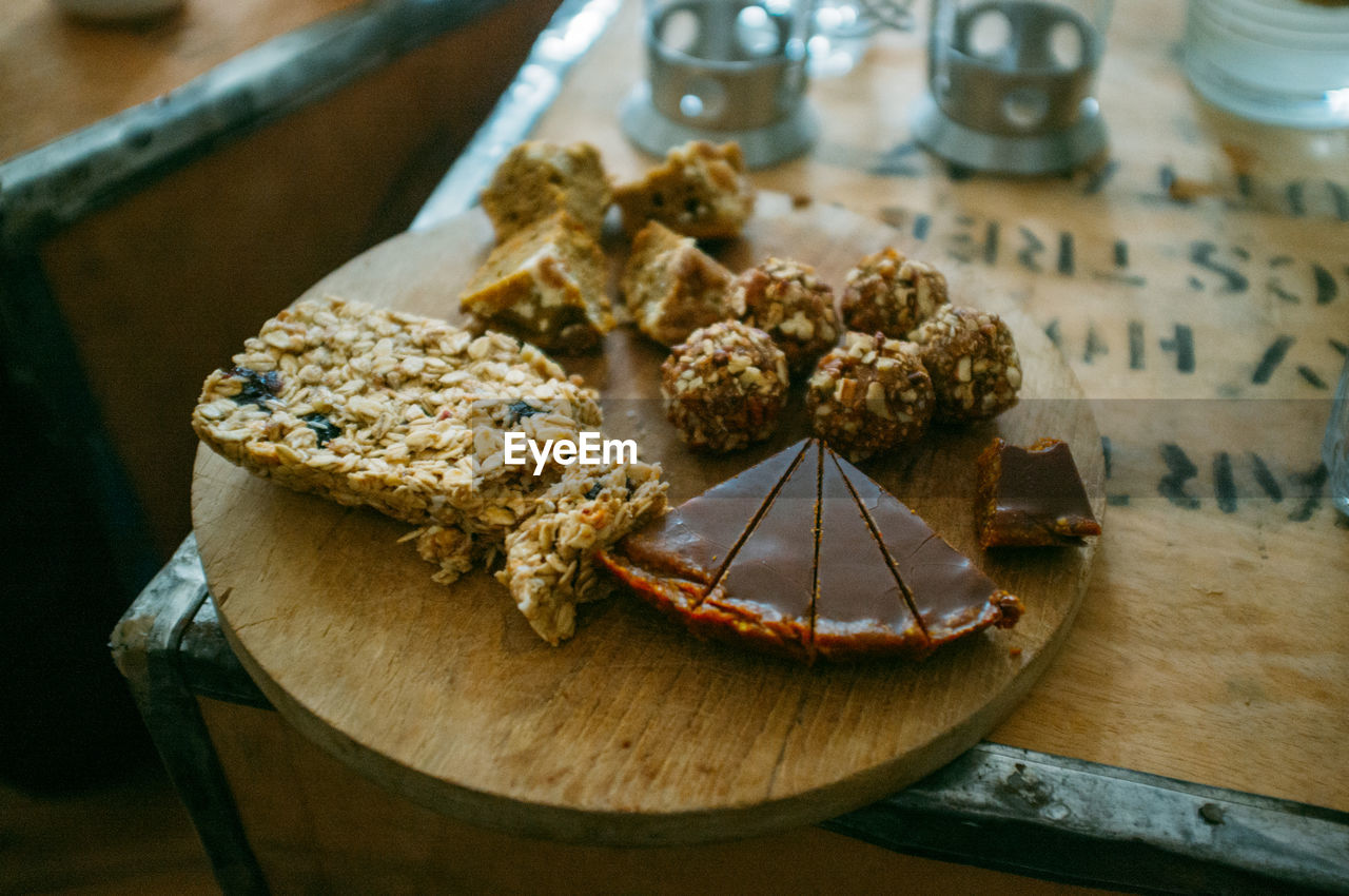 Close-Up Of Almond Balls And Chocolate Tart With Nut Bar On Cutting Board