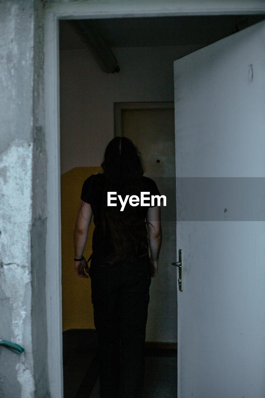 REAR VIEW OF WOMAN STANDING IN DOOR