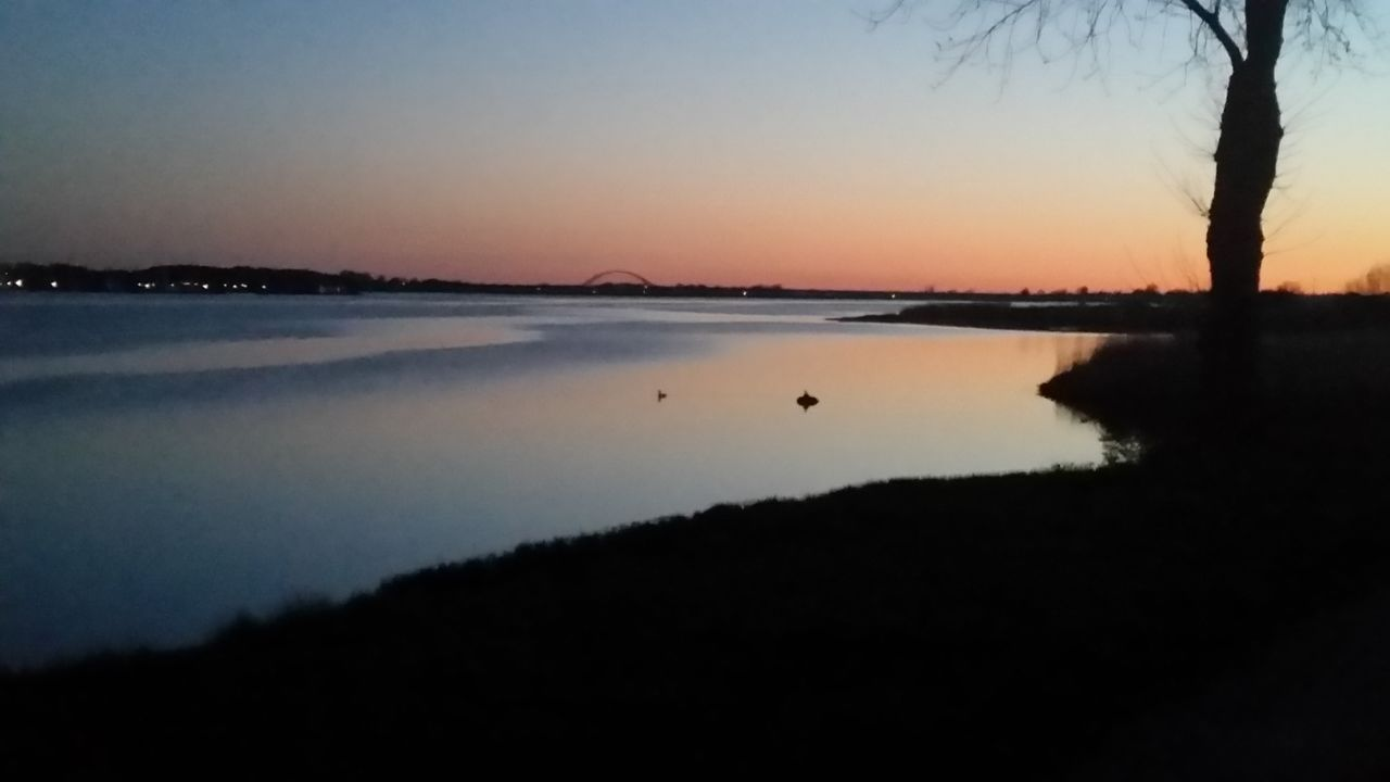 sky, tranquility, water, tranquil scene, sunset, scenics - nature, beauty in nature, silhouette, nature, copy space, lake, non-urban scene, idyllic, reflection, orange color, no people, clear sky, outdoors, beach
