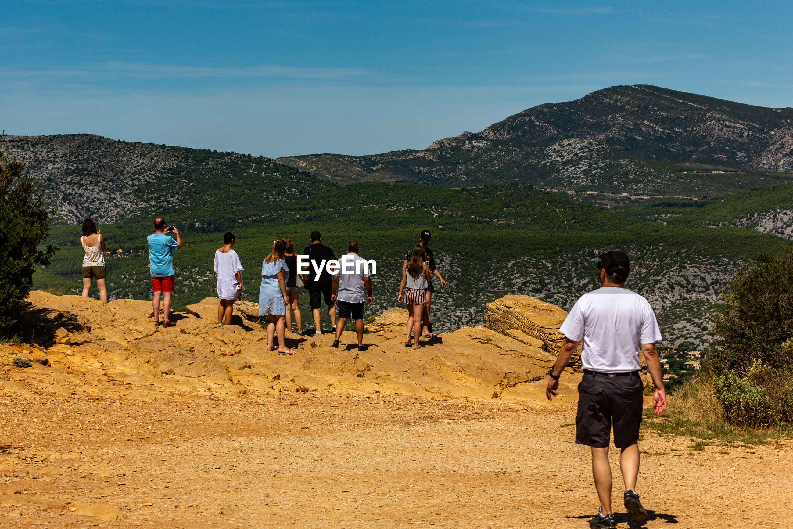 Rear view of people standing on mountain against blue sky during sunny day