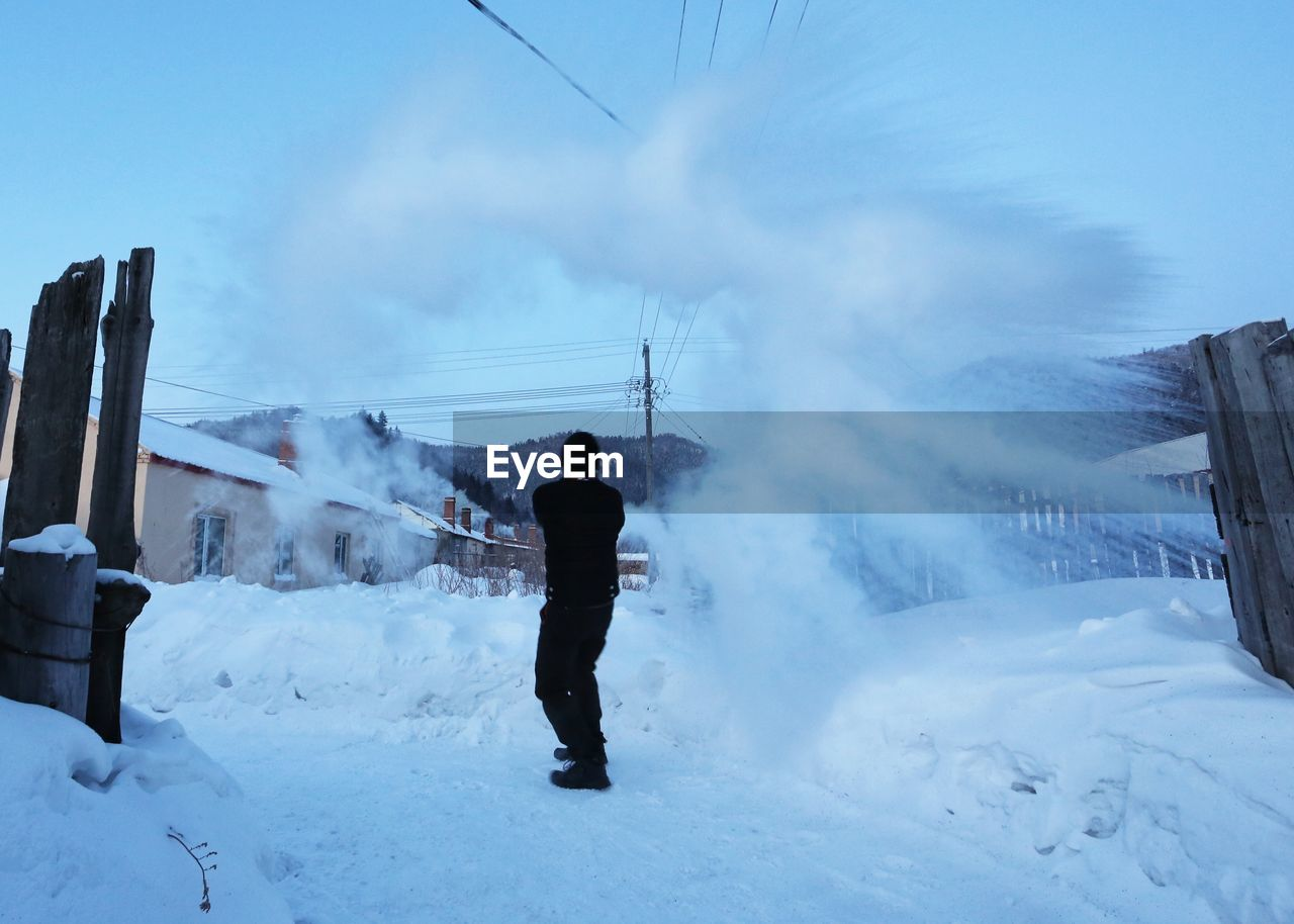FULL LENGTH REAR VIEW OF MAN STANDING ON SNOW COVERED LANDSCAPE