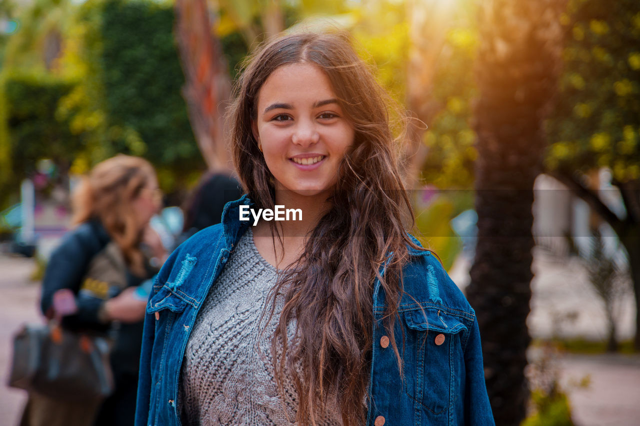 portrait, smiling, looking at camera, long hair, hairstyle, focus on foreground, hair, young adult, happiness, lifestyles, young women, one person, women, leisure activity, incidental people, real people, standing, casual clothing, front view, brown hair, beautiful woman, outdoors, teenager