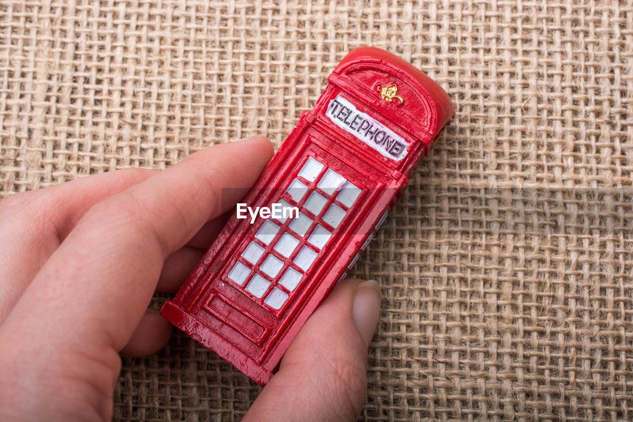 Cropped hand of person holding small telephone booth toy on table