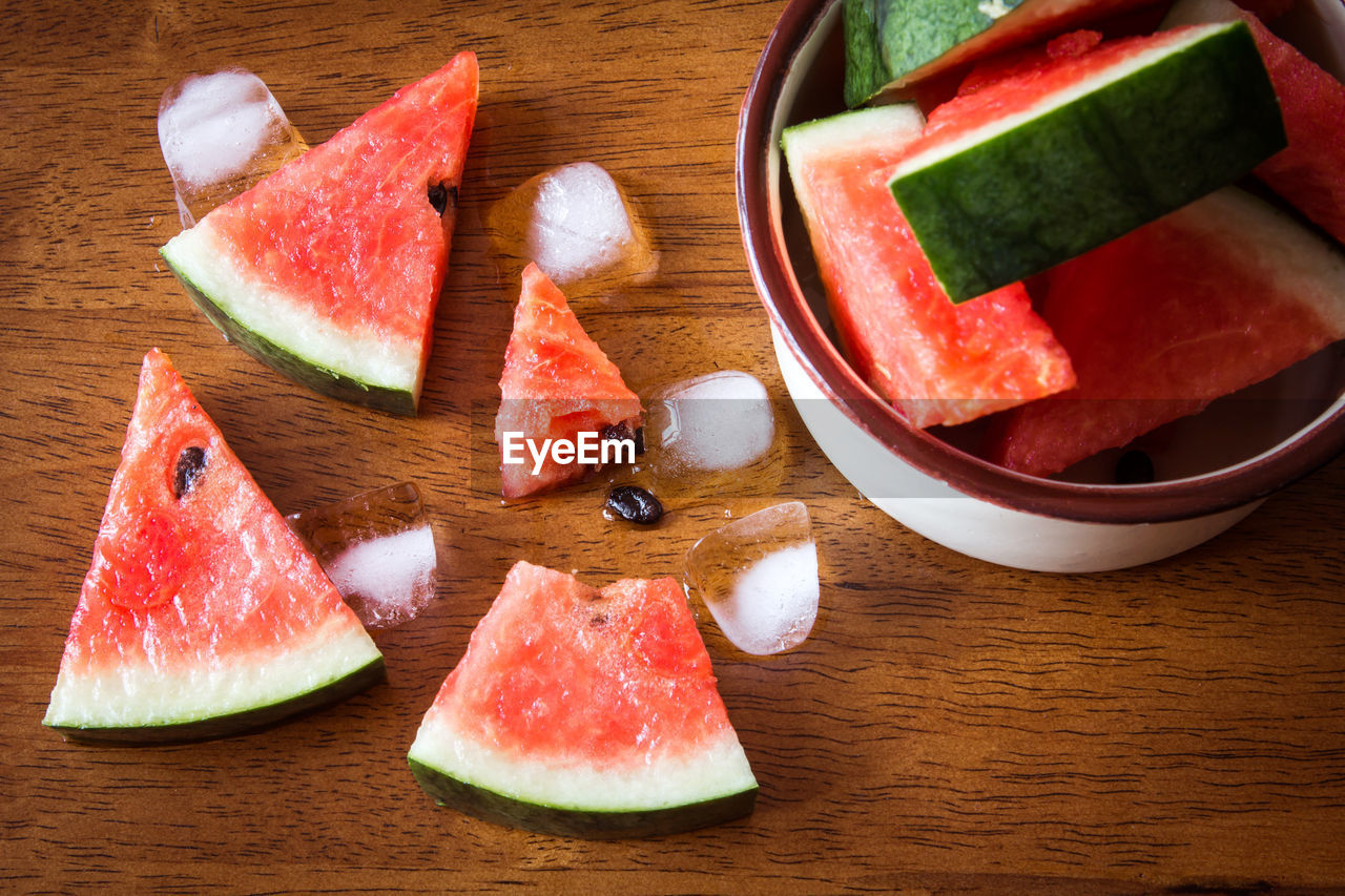 watermelon, food, food and drink, fruit, healthy eating, slice, wellbeing, freshness, table, red, melon, still life, no people, indoors, high angle view, wood - material, juicy, close-up, ripe, plate, chopped