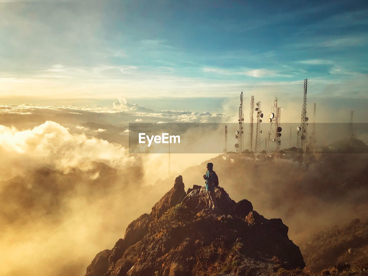cloud - sky, sky, beauty in nature, mountain, nature, scenics - nature, rock, real people, leisure activity, tranquil scene, tranquility, solid, outdoors, rock - object, day, adventure, people, non-urban scene, sitting, lifestyles, mountain peak, at the edge of