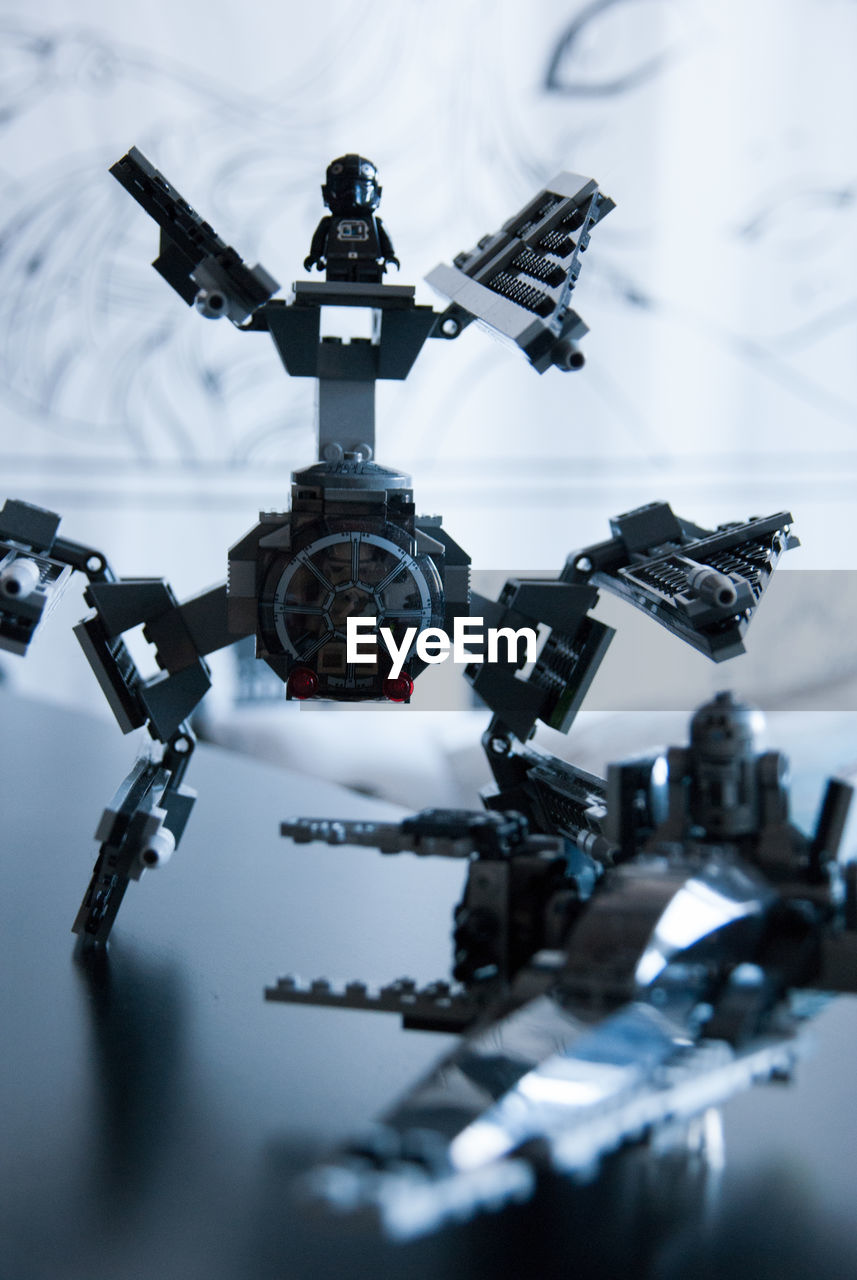 technology, no people, close-up, selective focus, day, robot, machinery, indoors, gun, futuristic, still life, security, black color, nature, focus on foreground, weapon, metal, connection, machine gun