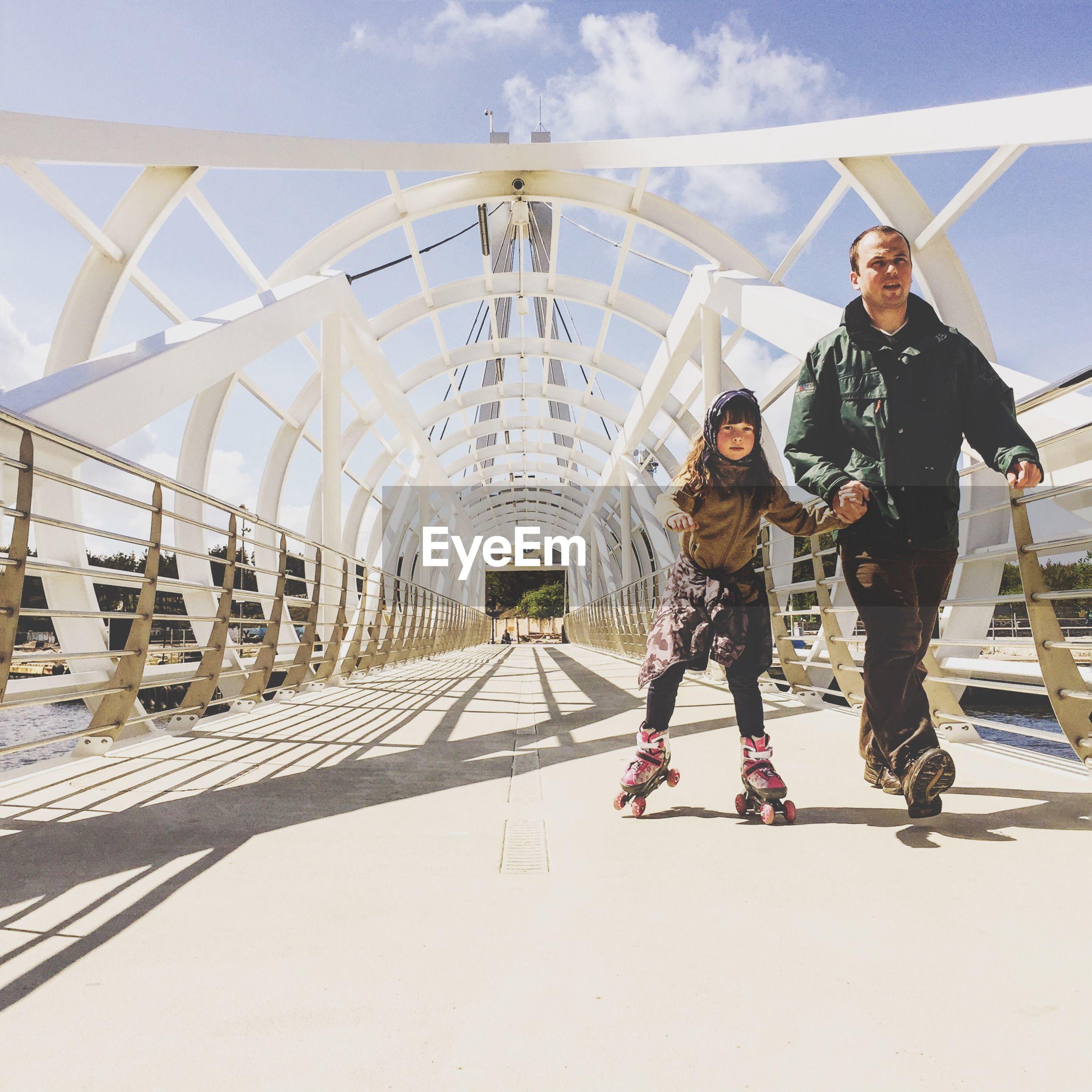 Full length of father holding daughter roller skating on footbridge