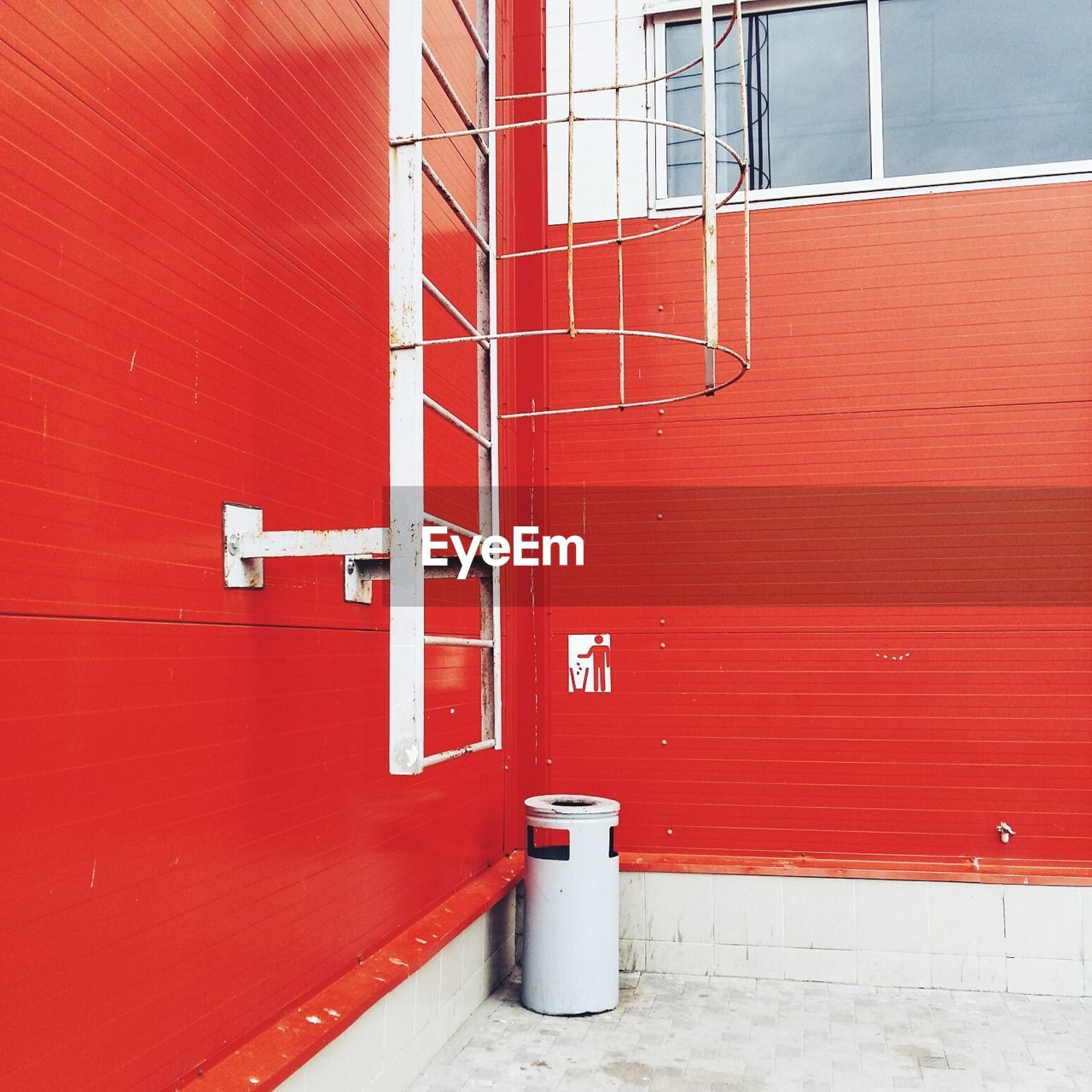 red, architecture, built structure, building exterior, wall - building feature, day, no people, metal, building, protection, safety, security, outdoors, window, pipe - tube, emergency equipment, wall, sunlight, white color, fire extinguisher