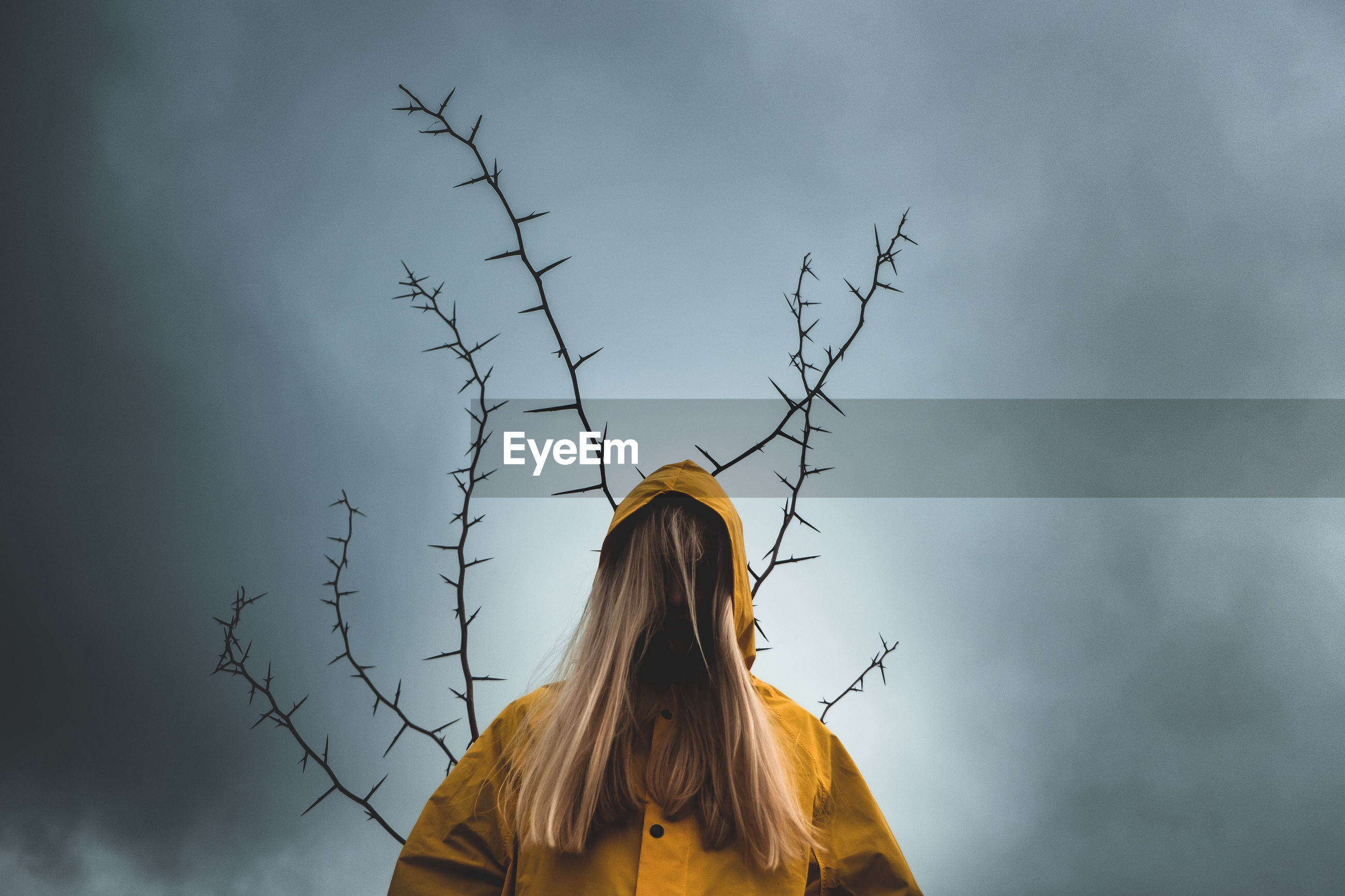 A girl with long hair in a yellow hood, with the back of a tree with thorns. concept of depression