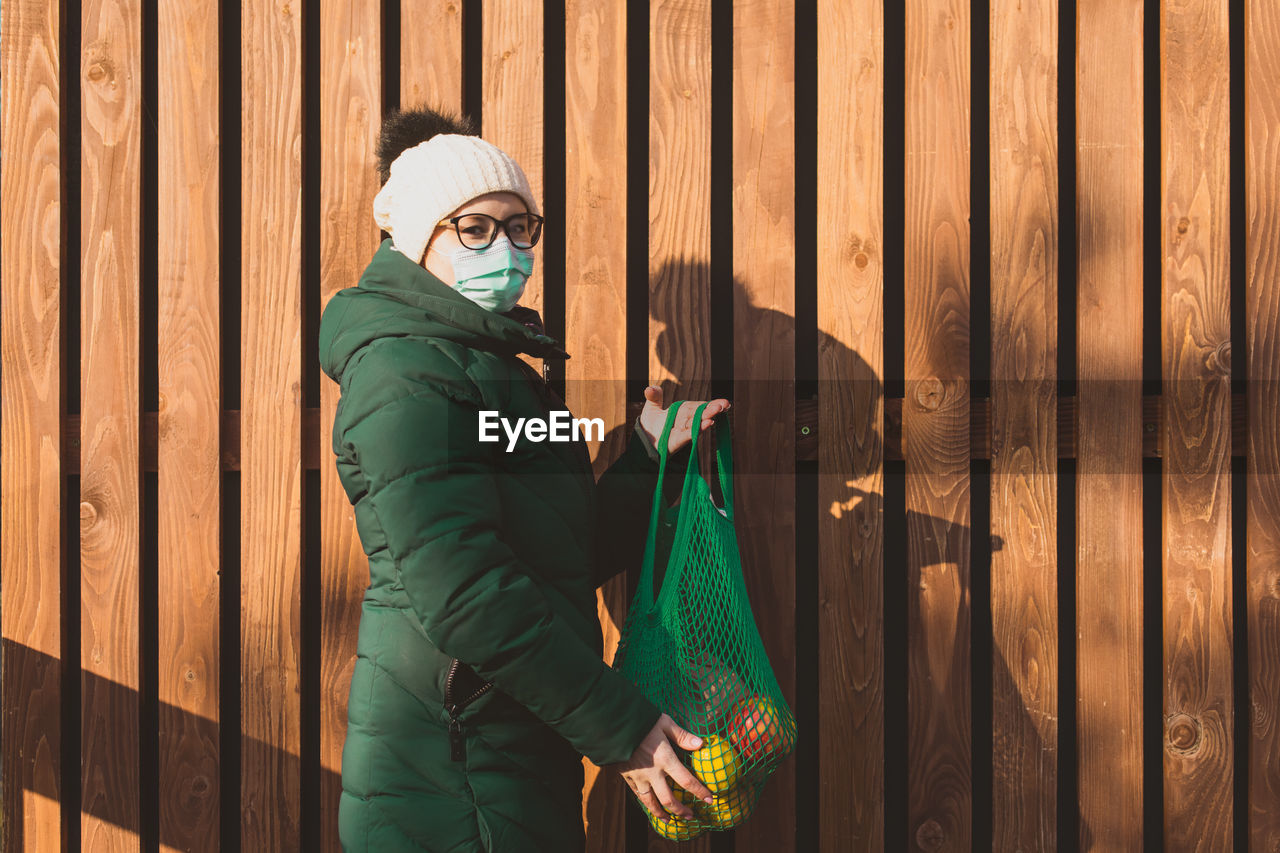 Woman with mesa bag against wooden wall