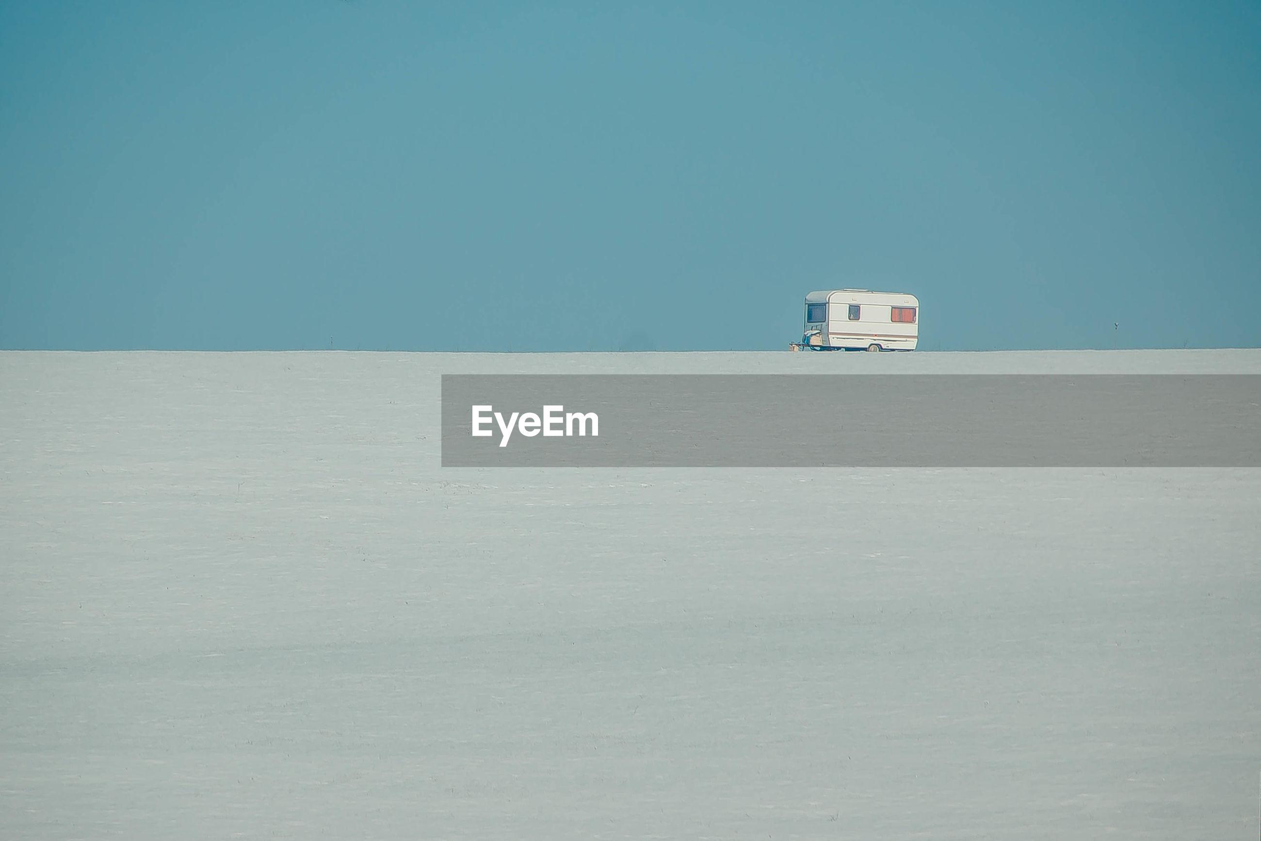 Lifeguard hut on sand against clear blue sky