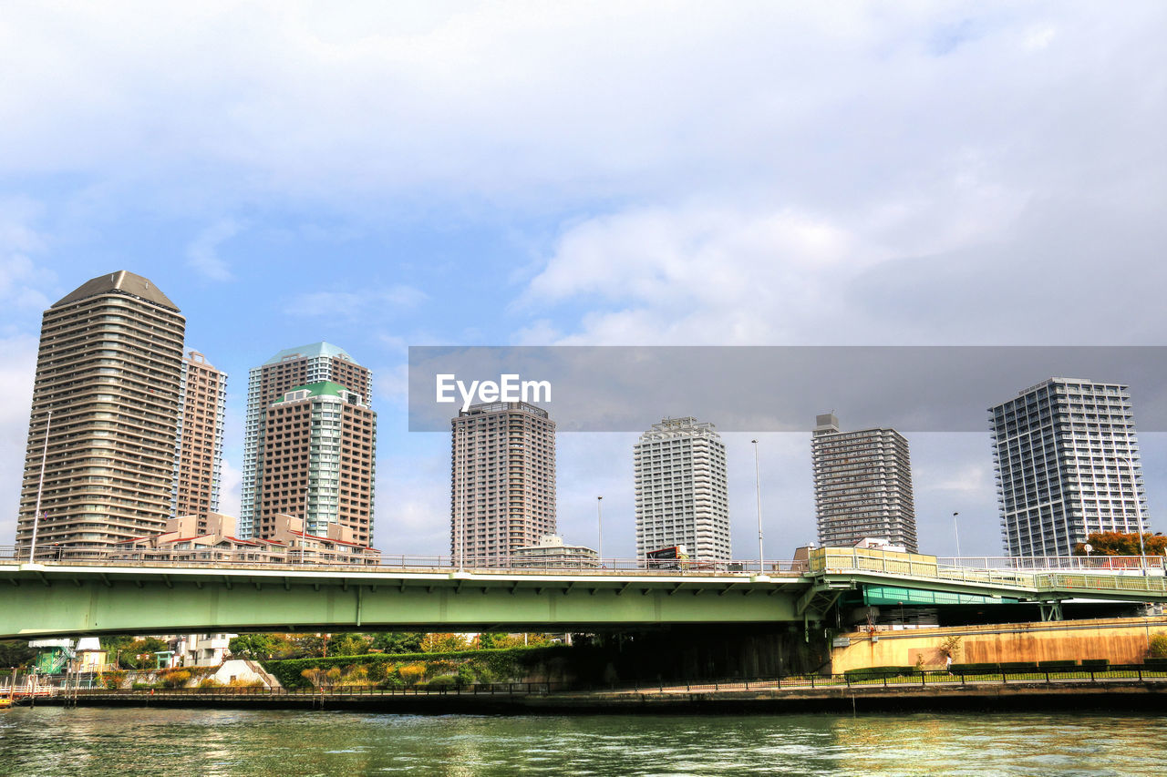 architecture, bridge - man made structure, built structure, river, connection, city, skyscraper, sky, building exterior, cloud - sky, water, outdoors, day, low angle view, waterfront, no people, modern, urban skyline, cityscape