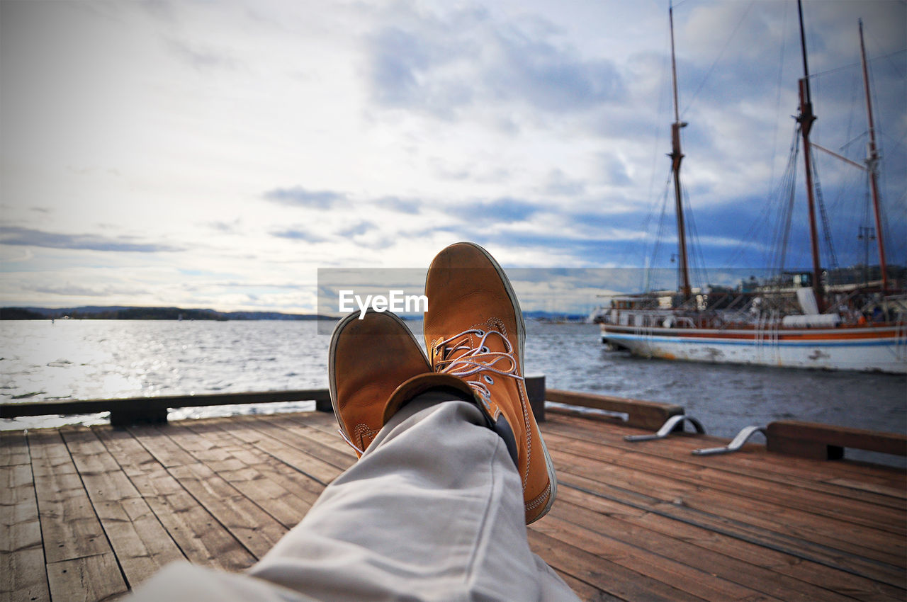Low section of man resting on jetty by boats moored at lake against sky