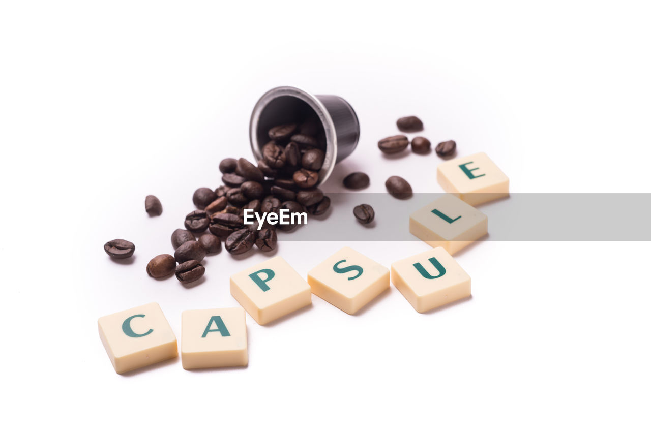 Close-up of capsule text with roasted coffee beans over white background