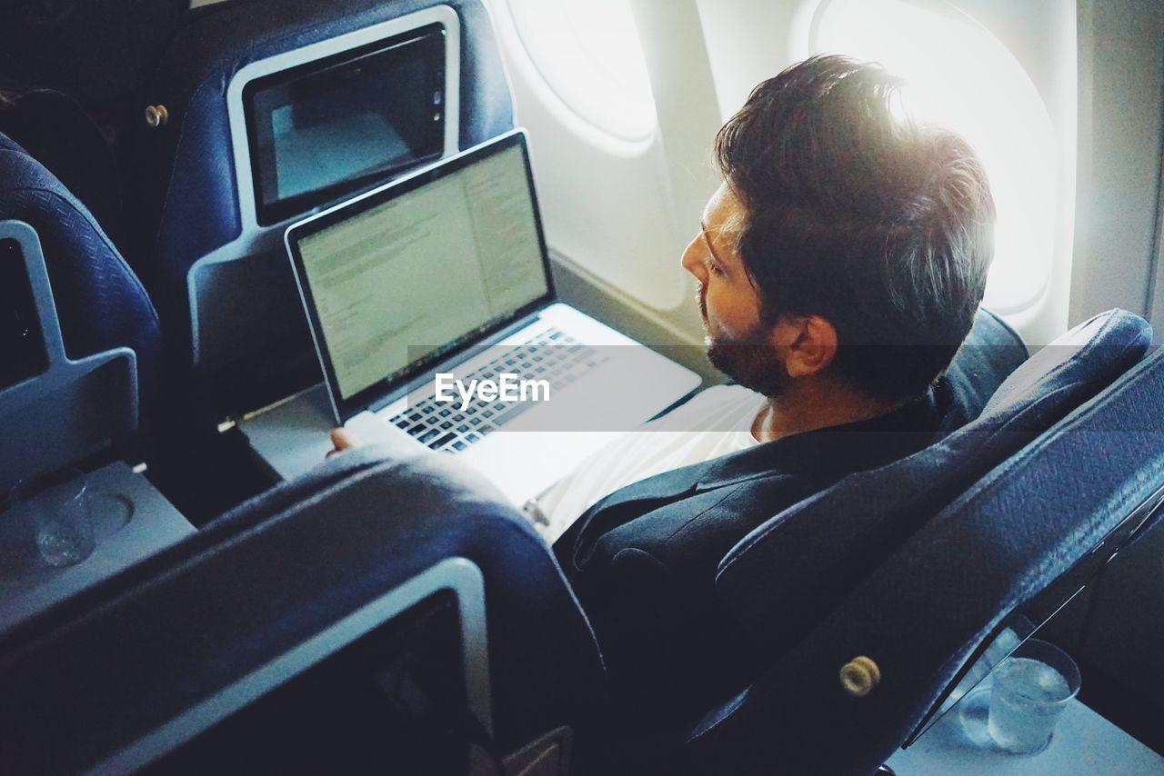 Man using laptop in airplane