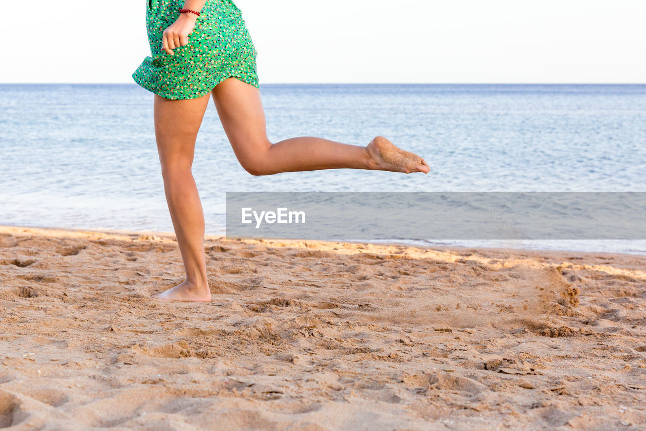 sea, water, beach, one person, land, horizon, horizon over water, sky, real people, leisure activity, human body part, nature, day, sand, human leg, holiday, vacations, trip, body part, outdoors, human limb