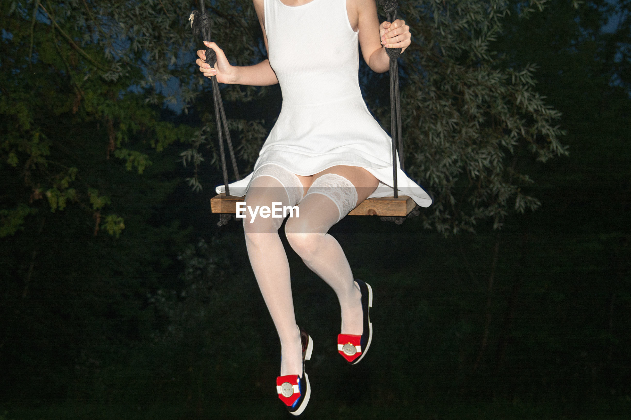 Low section of woman swinging against trees at night