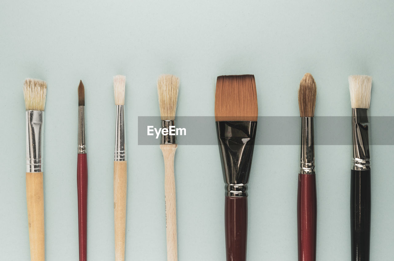 still life, brush, paintbrush, side by side, indoors, choice, variation, no people, wood - material, art and craft, close-up, creativity, group of objects, table, studio shot, medium group of objects, craft, white background, multi colored, collection, art and craft equipment