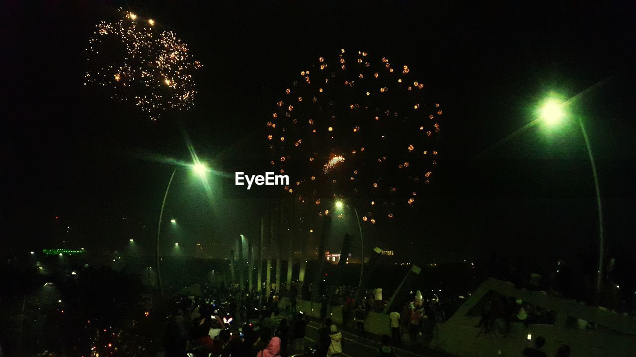 night, illuminated, arts culture and entertainment, celebration, low angle view, event, outdoors, large group of people, firework display, sky, tree, people