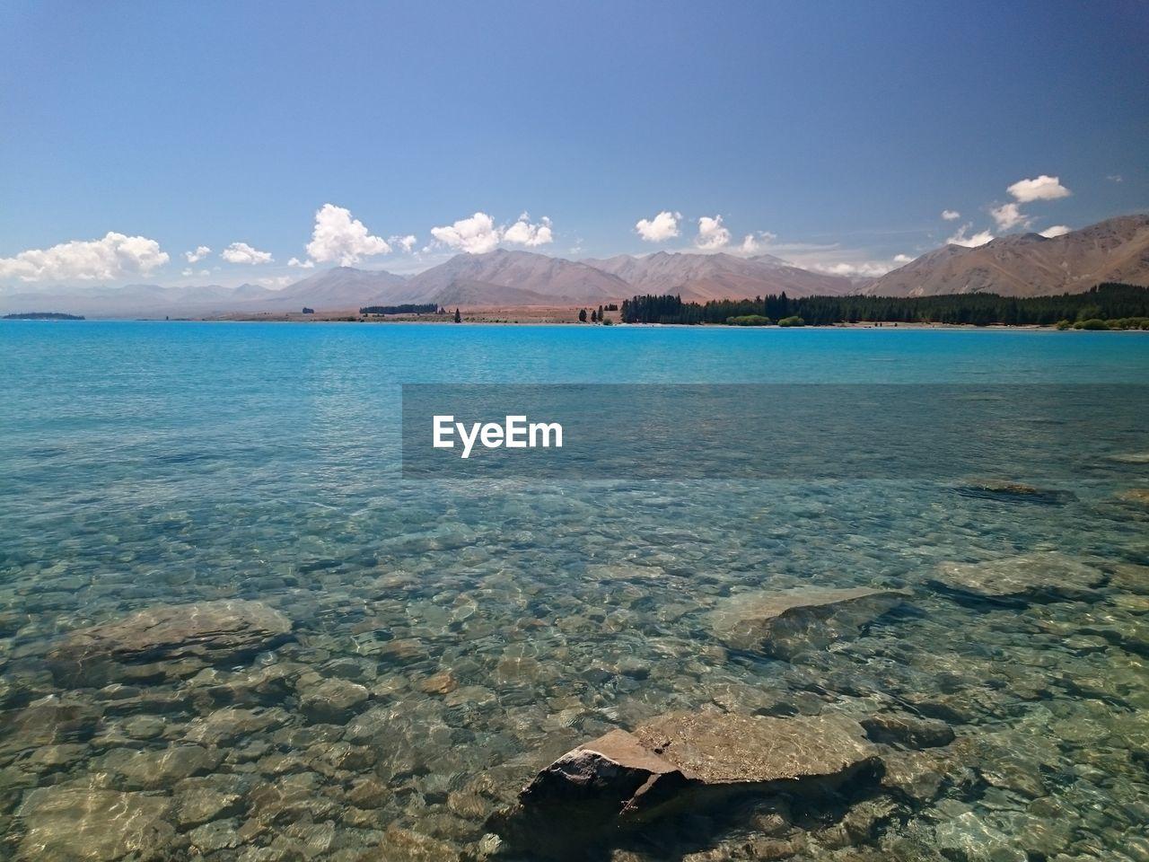 Idyllic shot of lake tekapo and mountains against sky