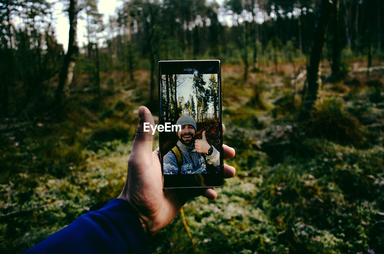 Cropped Hand Of Man Taking Selfie In Forest