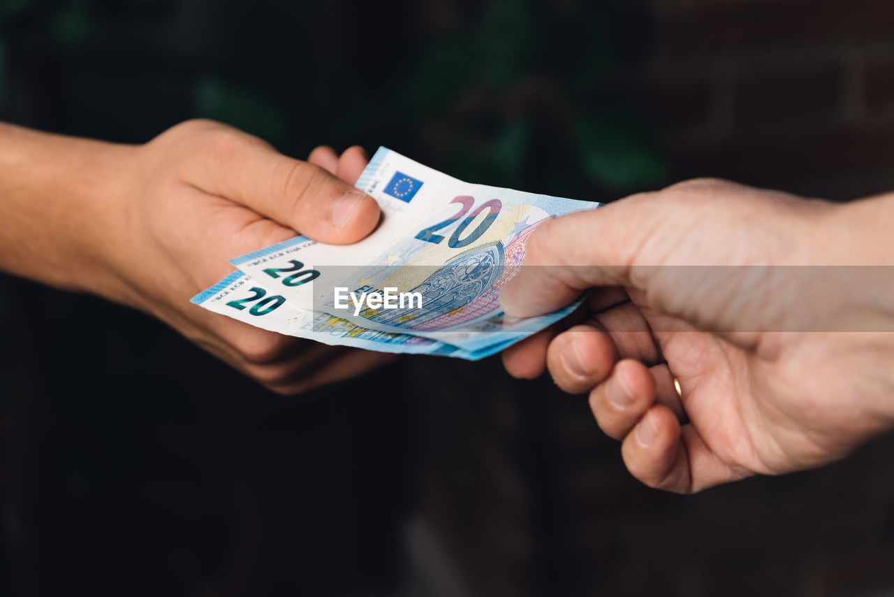 Cropped Image Of Hands Holding Paper Currency