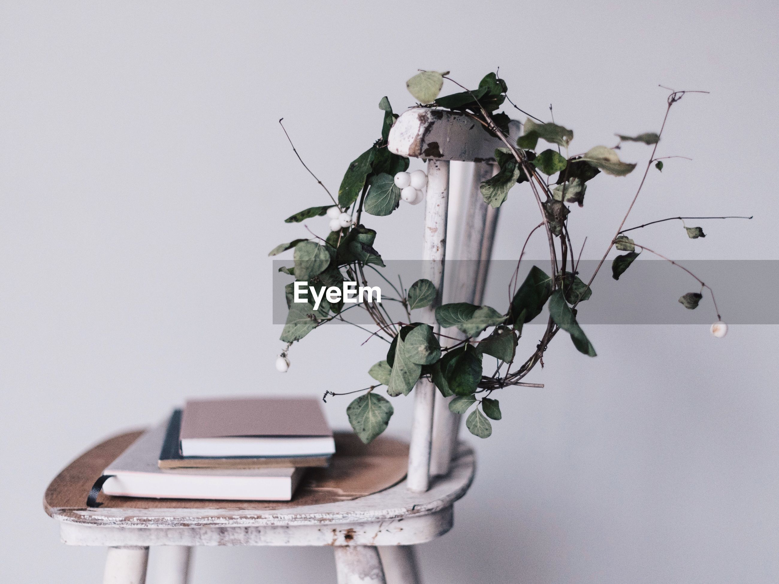 Wreath and books on chair against white wall